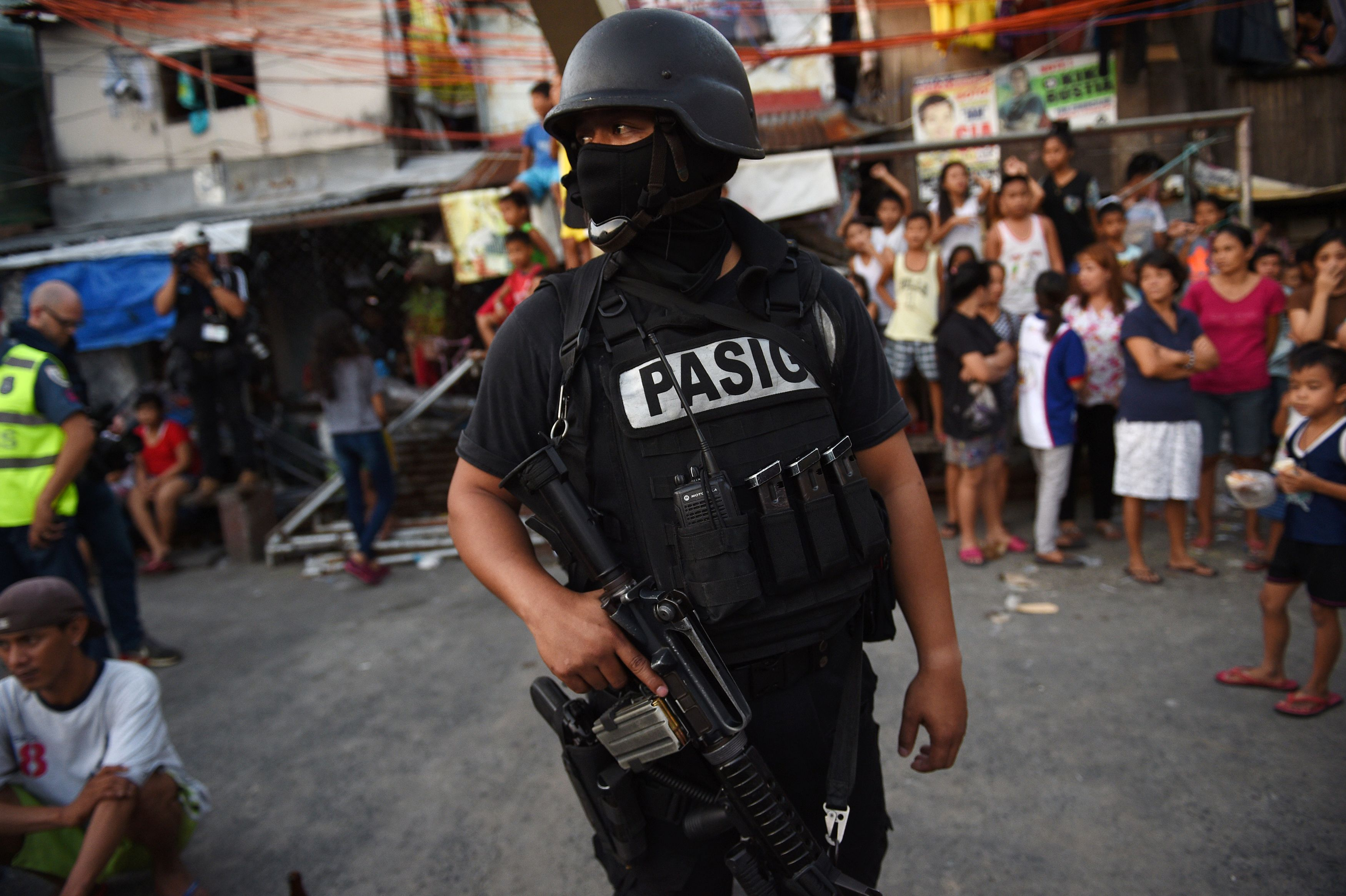 A member of the Special Weapons and Tactics (SWAT) team stands guard while residents look on during an antidrug operation at an informal settlers area in Manila on Nov. 9, 2016. Since President Rodrigo Duterte took office on June 30, his war on drugs and other crimes have claimed more than 4,100 lives, according to official figures