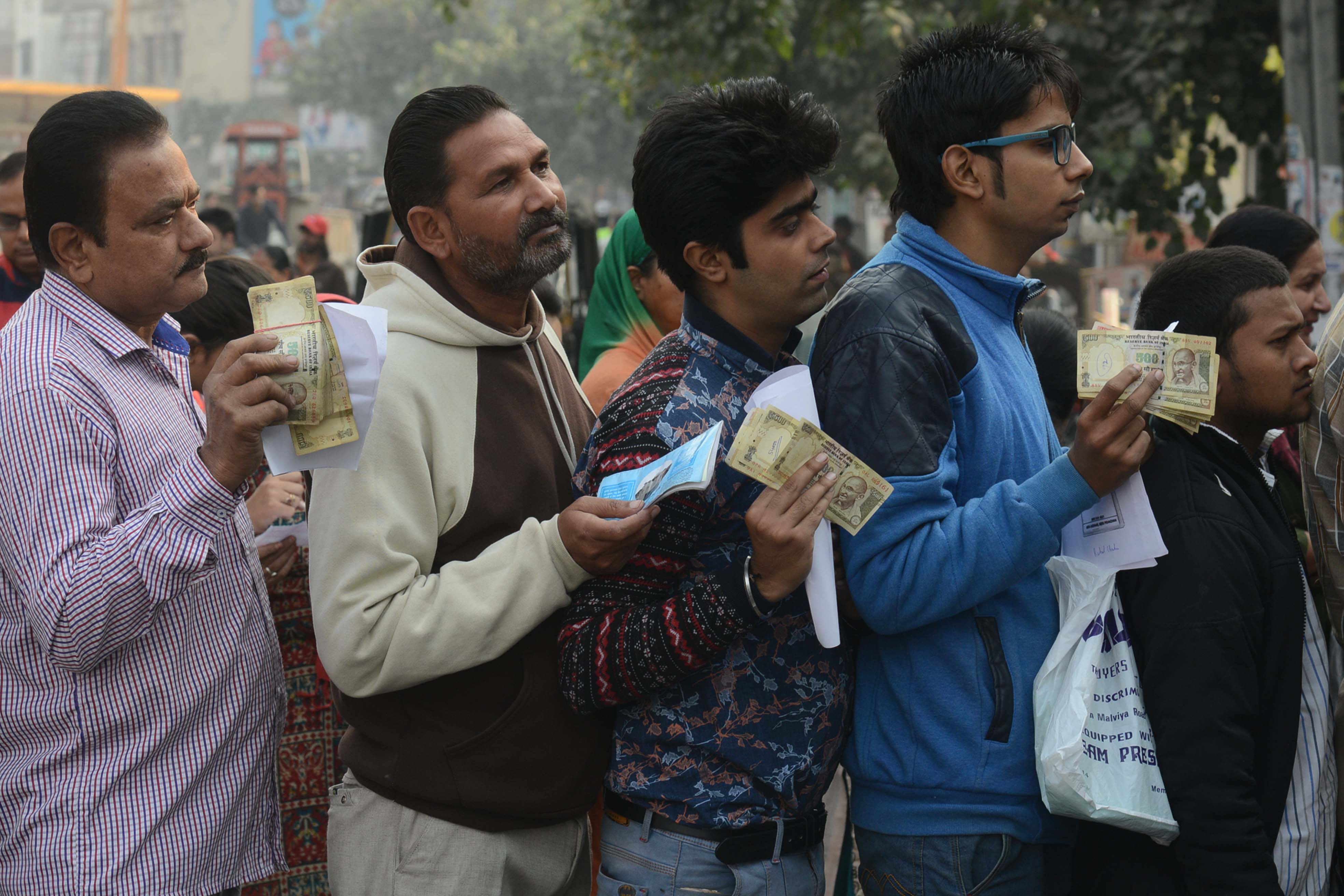 Indian people queue outside a bank as they wait to deposit and exchange 500 and 1000 rupee notes in Amritsar on November 13, 2016.