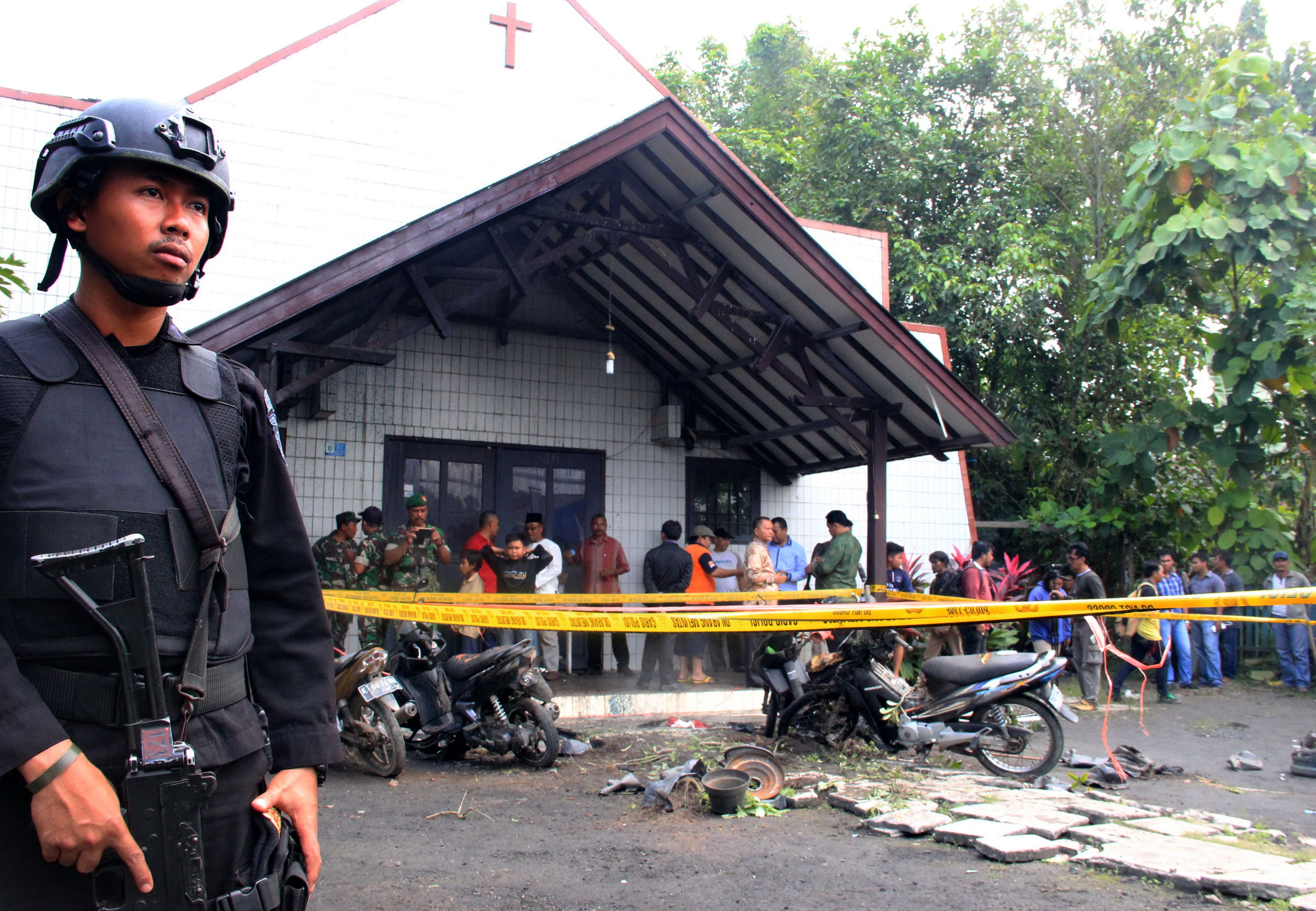 An Indonesian policeman stands guard outside the Oikume Church  in Samarinda, Indonesia's East Kalimantan province, on Nov. 13, 2016, after a man allegedly threw a Molotov cocktail toward it, killing a child and wounding three others