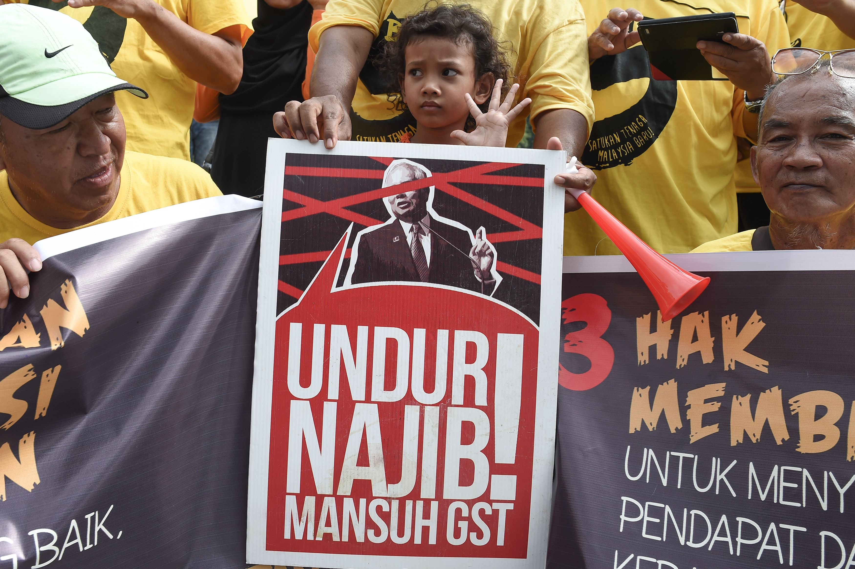 A child stands behind a placard reading  Step Down Najib  as members of civil society alliance Bersih pose for pictures on on Nov. 11, 2016, in the Malaysian town of Ipoh, ahead of their demonstration in  Kuala Lumpur to demand Najib's resignation