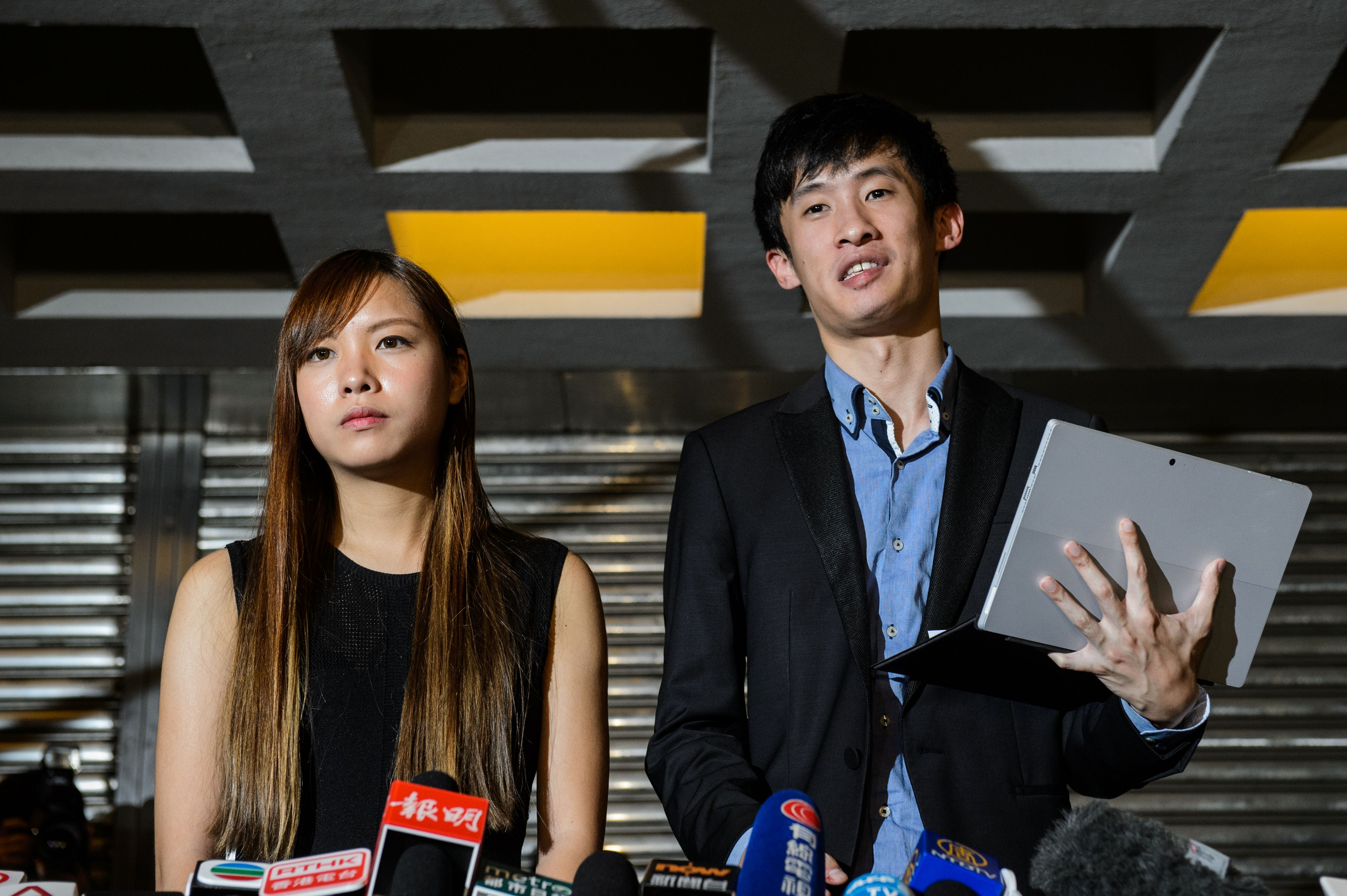 Pro-independence lawmakers Sixtus  Baggio  Leung, right. and Yau Wai-ching speak to the press outside the High Court in Hong Kong on Nov. 15, 2016, after a court ruled to disqualify them as lawmakers