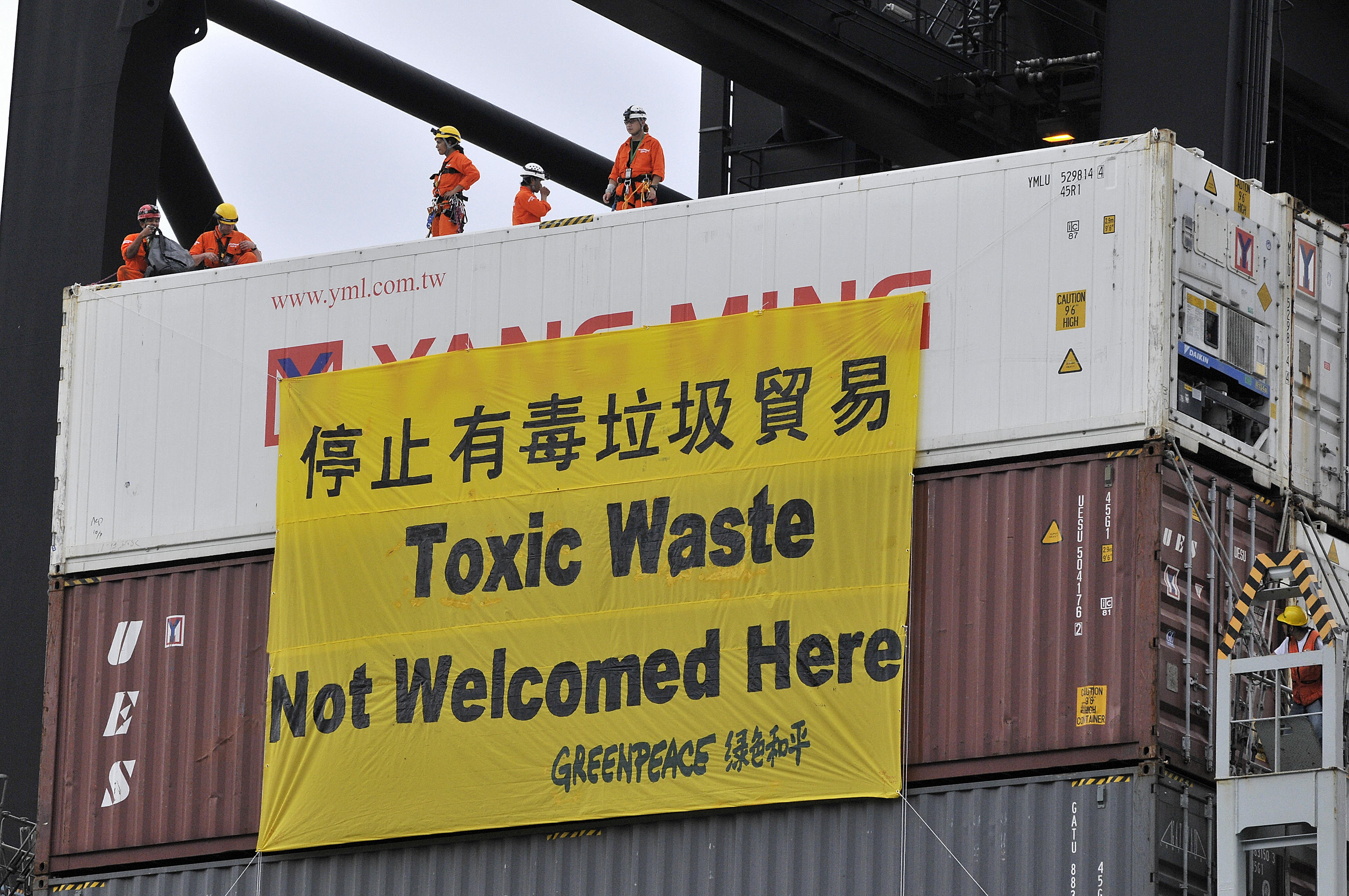 Greenpeace activists lower a banner on a cargo ship allegedly carrying illegal US electronic waste shipment in Hong Kong on June 14, 2008