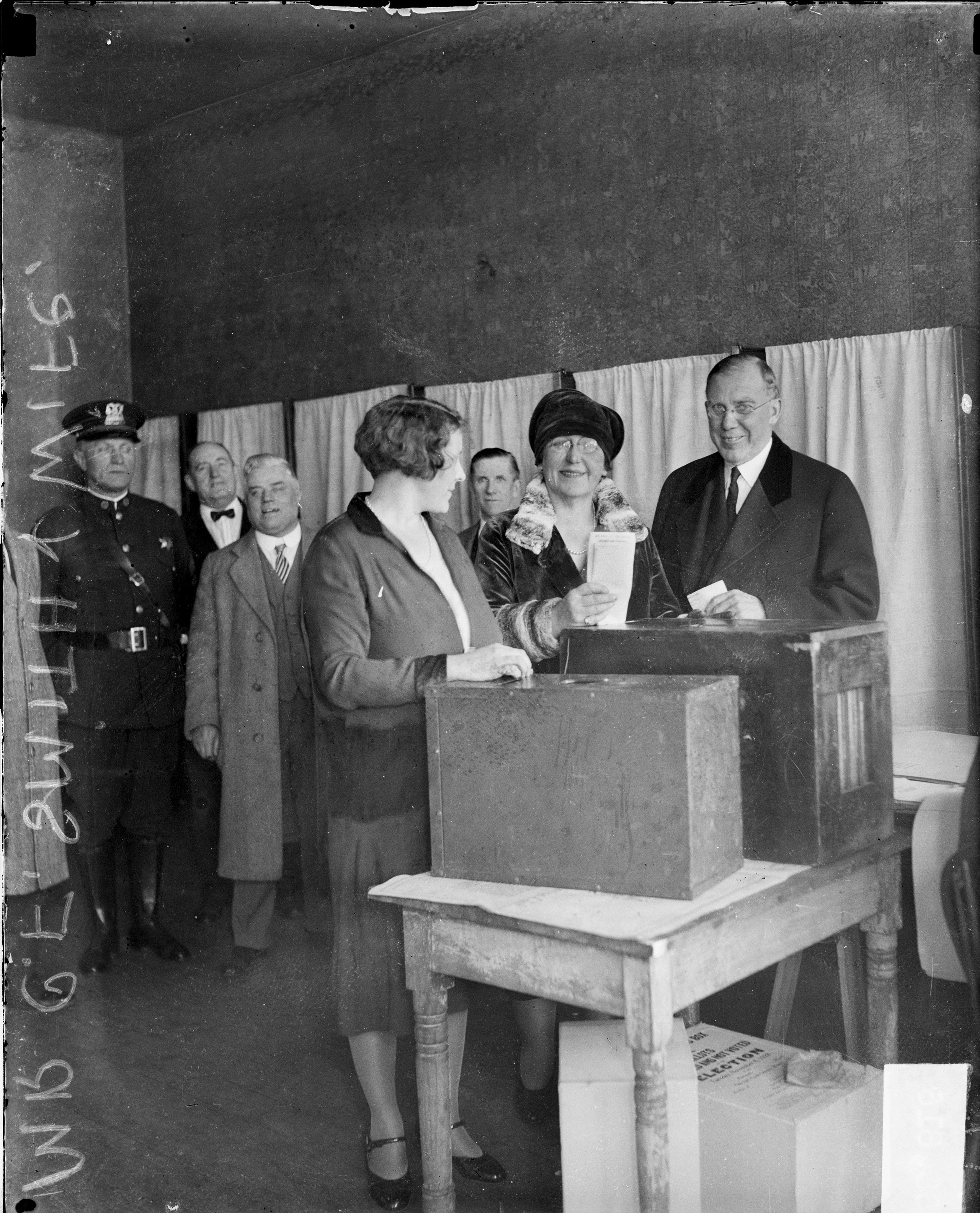 Clayton F. Smith, Deputy Commissioner of City Works, and his wife, Mayme Paschen, looking toward the camera, standing next to a ballot box at a voting poll center in Chicago, in 1928.