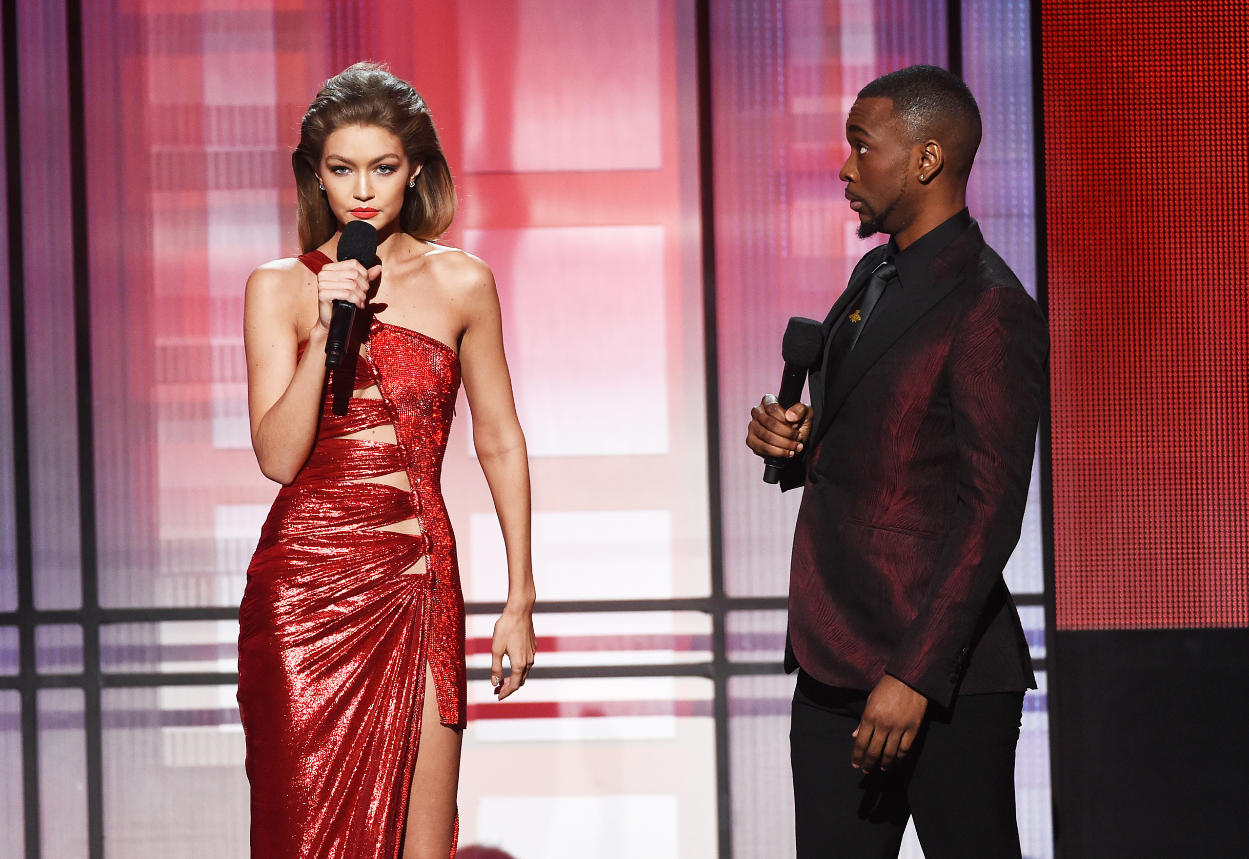 Co-hosts Gigi Hadid (L) and Jay Pharoah speak onstage during the 2016 American Music Awards at Microsoft Theater in Los Angeles, California, on Nov. 20, 2016.