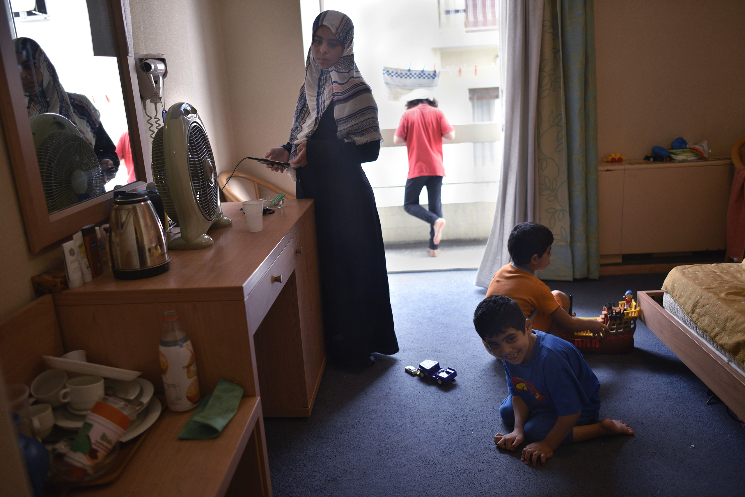 Baida, 27, from Raqqa, Syria, keeps an eye on her three children as they play in her family's room at the hotel. Her youngest son, 7-year-old Ahmed, has cerebral palsy and cannot walk. He has a wheelchair, but because the elevators are not working in the eight-floor building, the family keeps the wheelchair downstairs in the lobby.