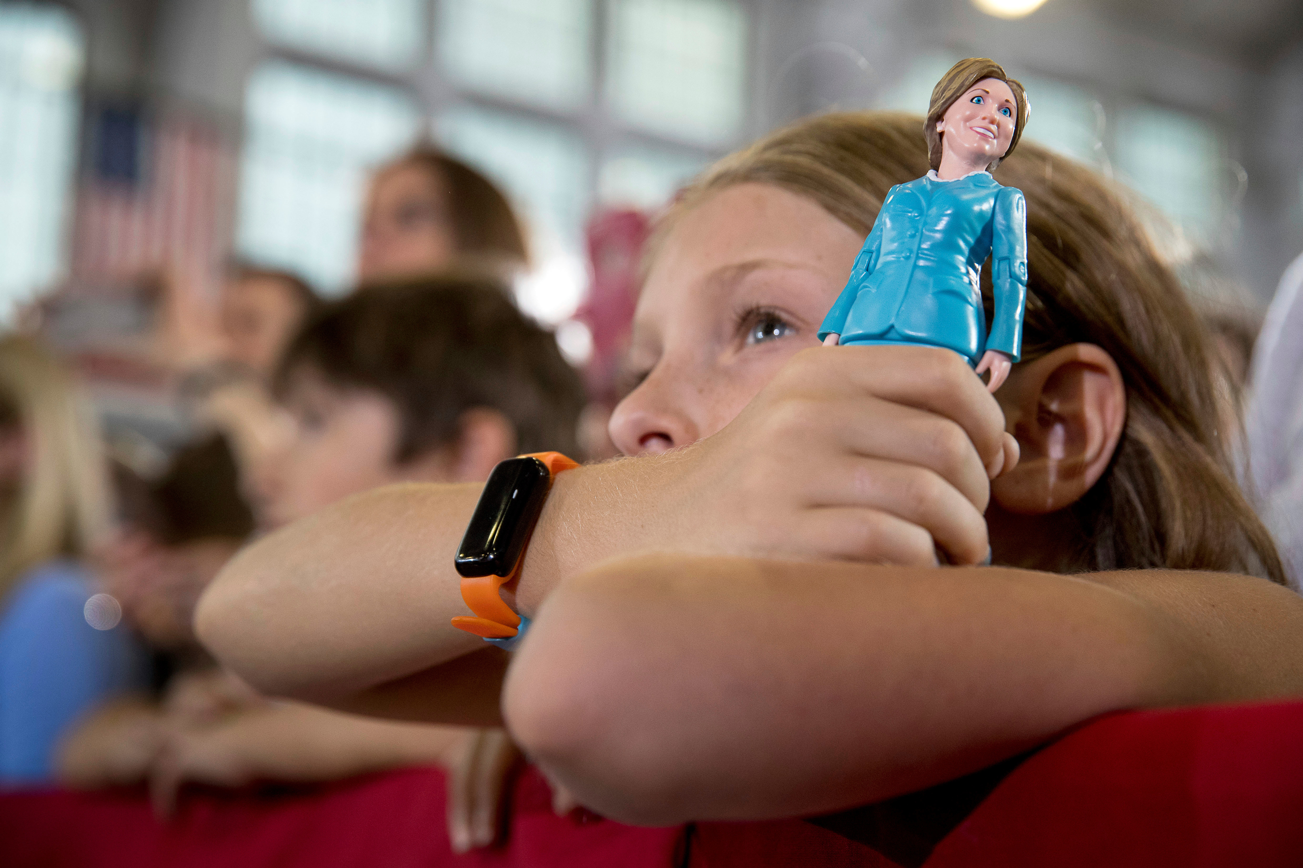 A girl in the audience holds a figurine of Democratic presidential candidate Hillary Clinton as Clinton speaks at a rally at Goodyear Hall and Theater in Akron, Ohio, on Oct. 3, 2016.