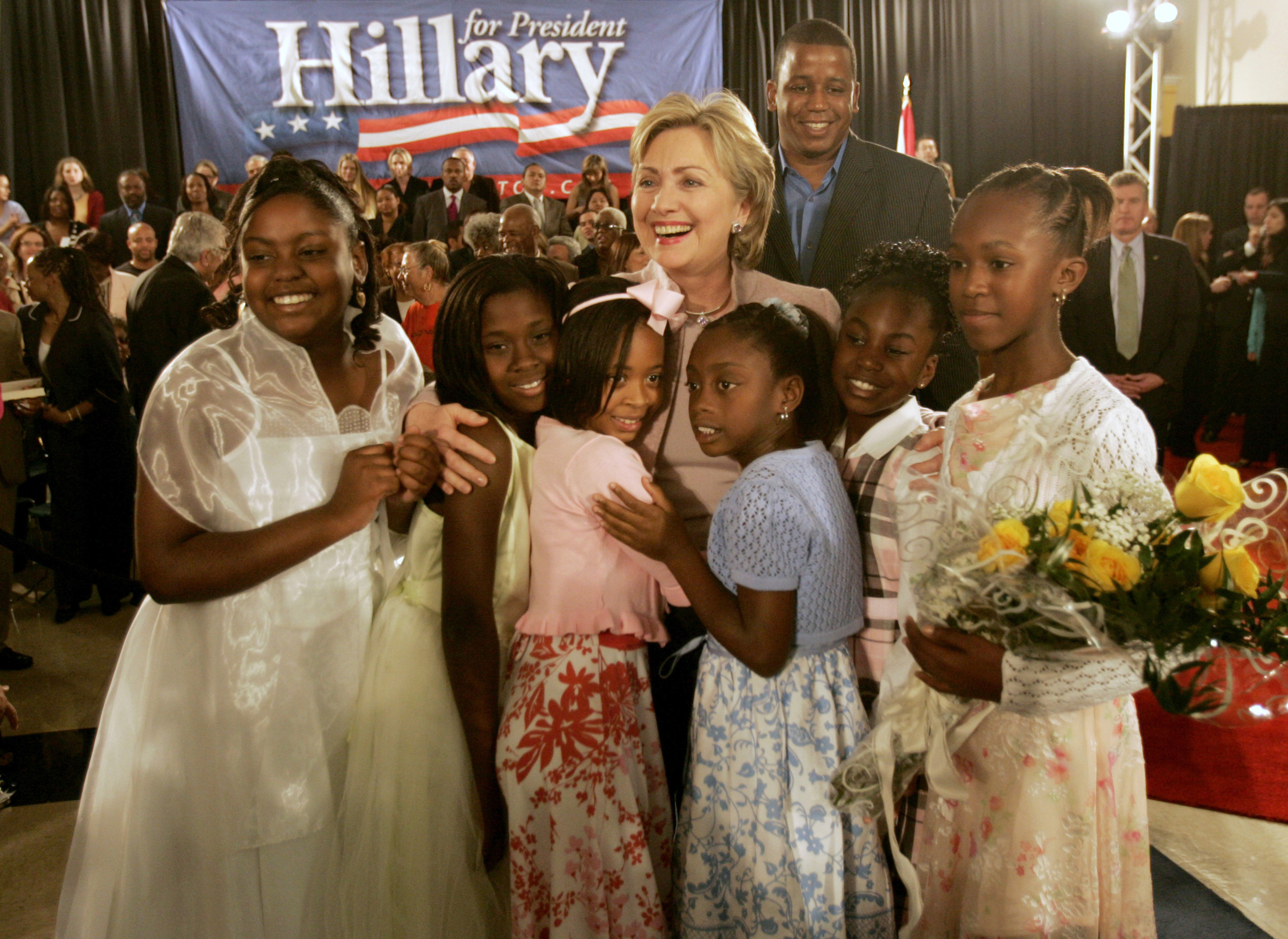 Hillary Rodham Clinton is hugged by girls who presented her with flowers at the Joseph Caleb Center in Miami, on Feb. 20, 2007.