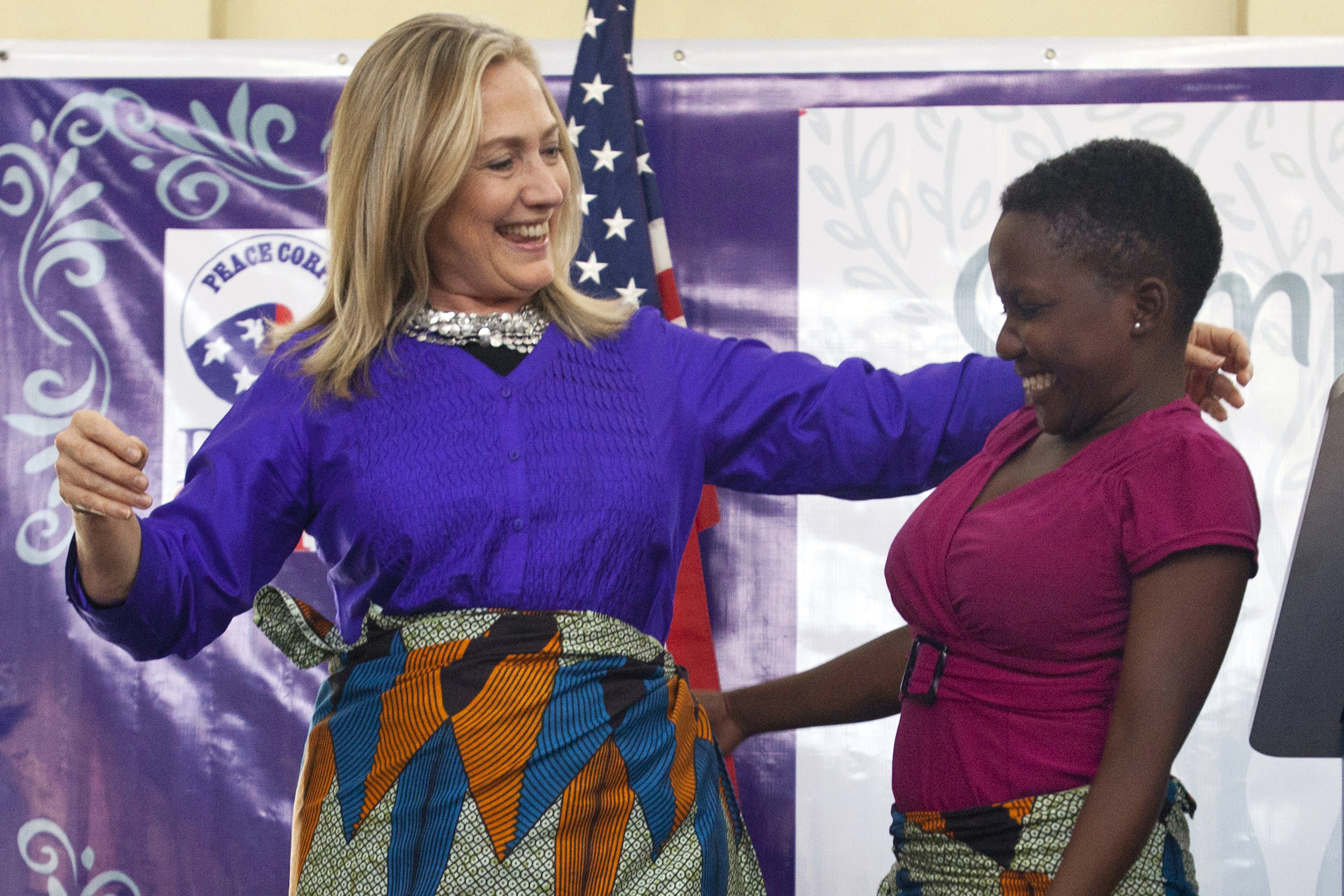 Hillary Clinton embraces Triza Lapani, 17, after  the teen helped Clinton put on a chitenje cloth, a traditional skirt, after speaking at Camp GLOW (Girls Leading Our World) run by the Peace Corps, in Lilongwe, Malawi on Aug. 5, 2012.