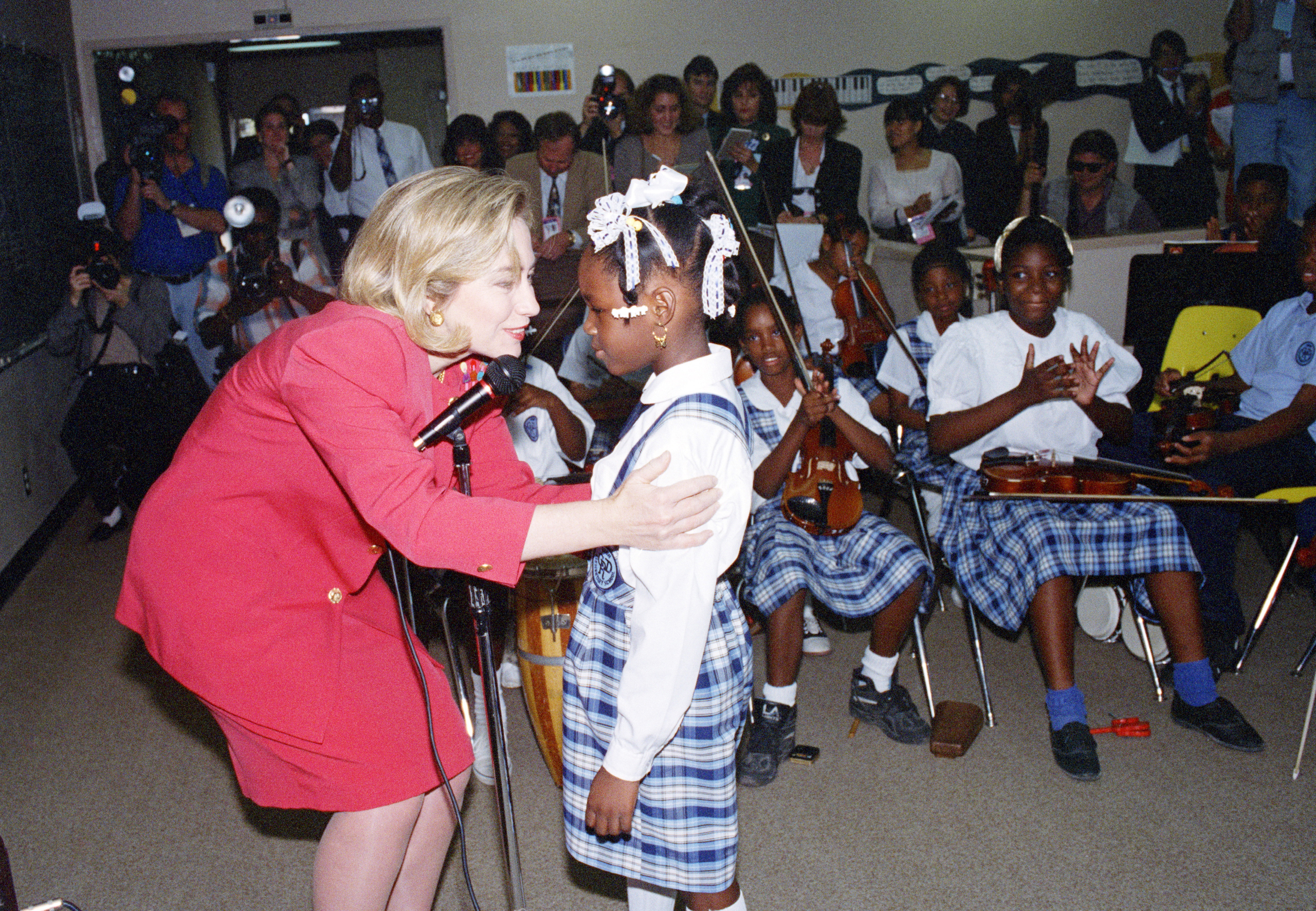 """Hillary Clinton thanks six-year-old Shantelle Williams, 6, after the girl serenaded Mrs. Clinton with Whitney Houston's hit """"I Will Always Love You"""" during a visit to Drew Elementary School in Miami, Florida on Dec. 9, 1994."""