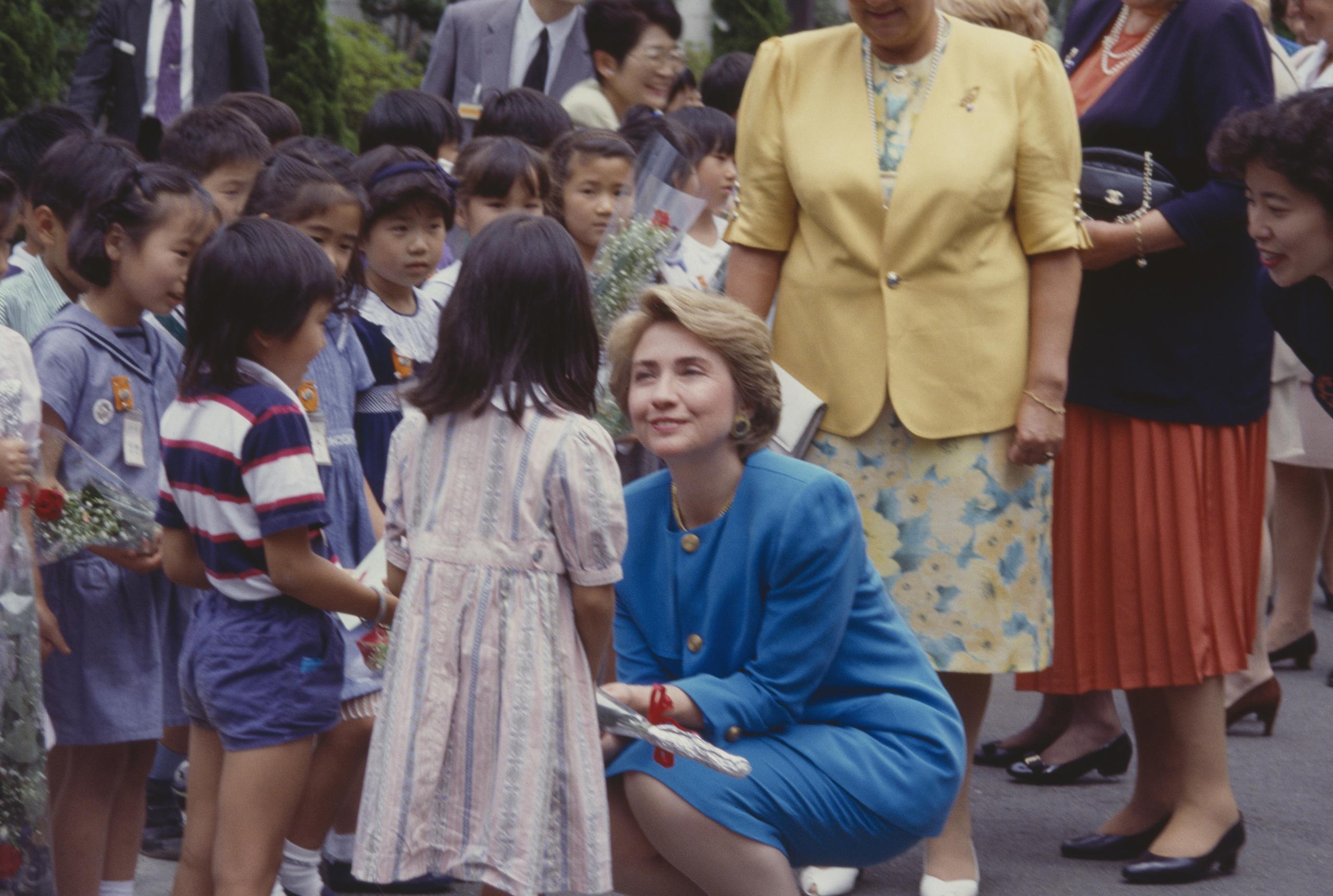 Hillary Clinton talking to children in a crowd, circa 1994.