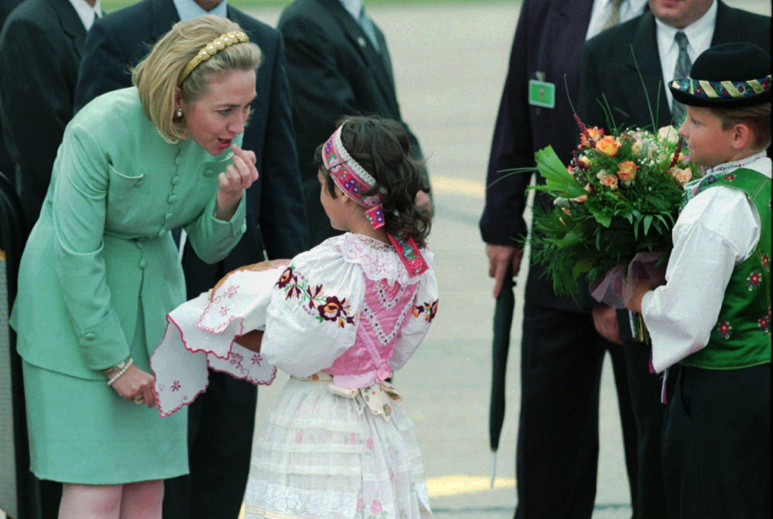 A young Slovakian girl welcomes Hillary Clinton in a traditional manner with bread and salt as she arrives at Bratislava's airport on July 6, 1996.