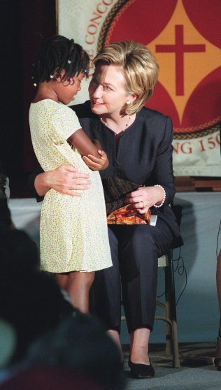 US First Lady Hillary Clinton (R) accepts a gift f