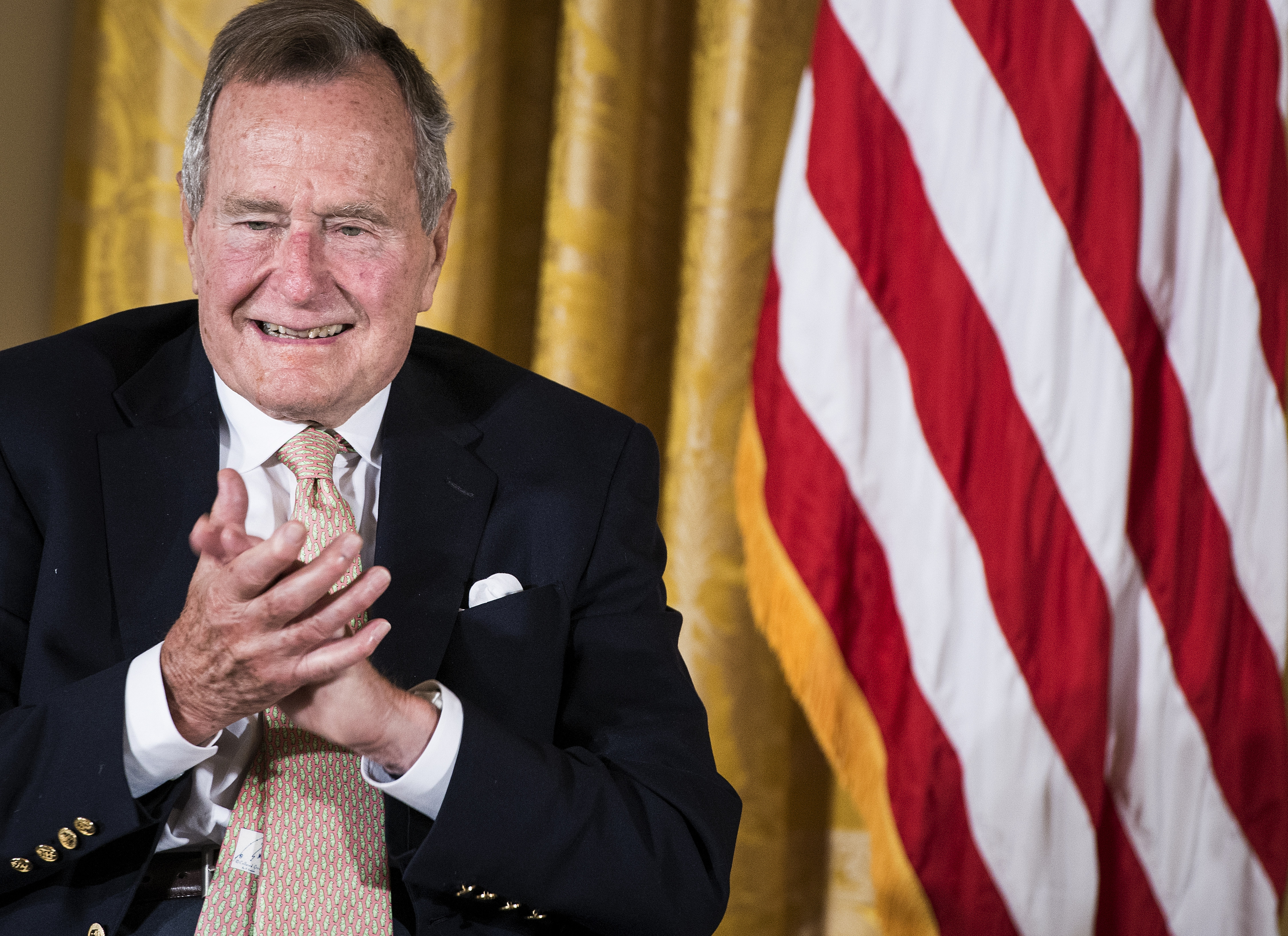 Former US President George H. W. Bush applauds during an event in the East Room of the White House July 15, 2013 in Washington, DC.