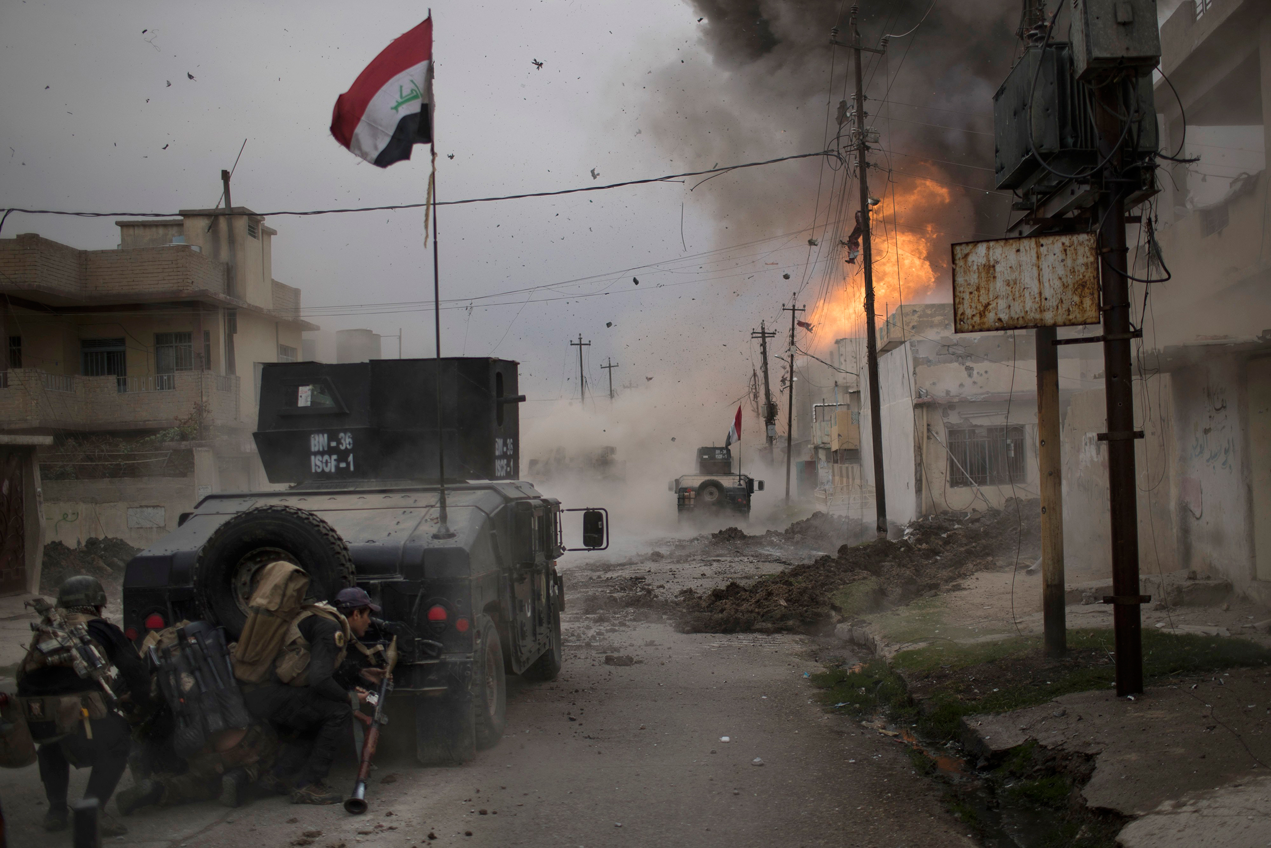 A car bomb explodes next to armored vehicles belonging to Iraqi Special Forces as they advance toward ISIS-held territory in Mosul on Nov. 16, 2016. Troops have established a foothold in the city's east from where they are driving northward into the Tahrir neighborhood.