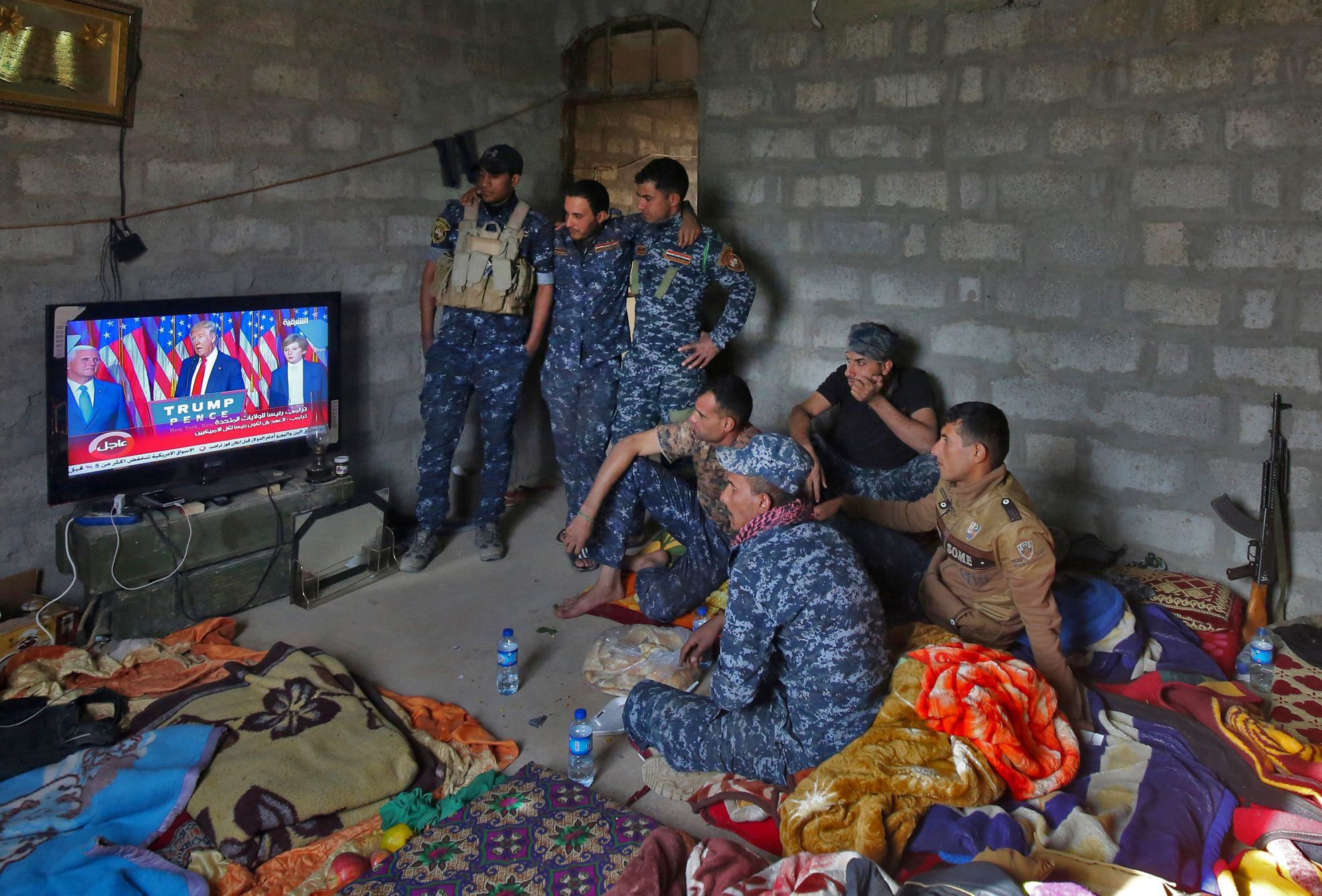 Members of the Iraqi forces watch President-elect Donald Trump give a speech after he won the U.S. presidential elections on a TV set while resting in the village of Arbid, on the southern outskirts of Mosul, on Nov. 9, 2016.