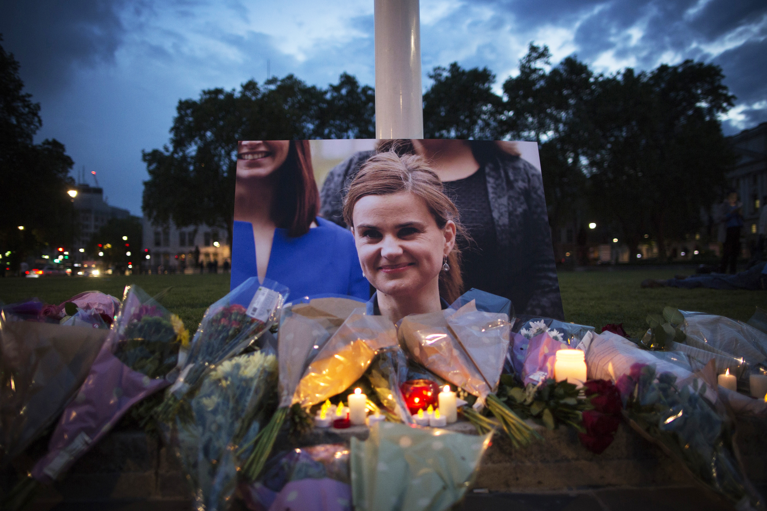 Flowers surround a picture of Jo Cox during a vigil in Parliament Square on June 16, 2016. The trial of the man suspected of killing Cox, Thomas Mair, started this week.