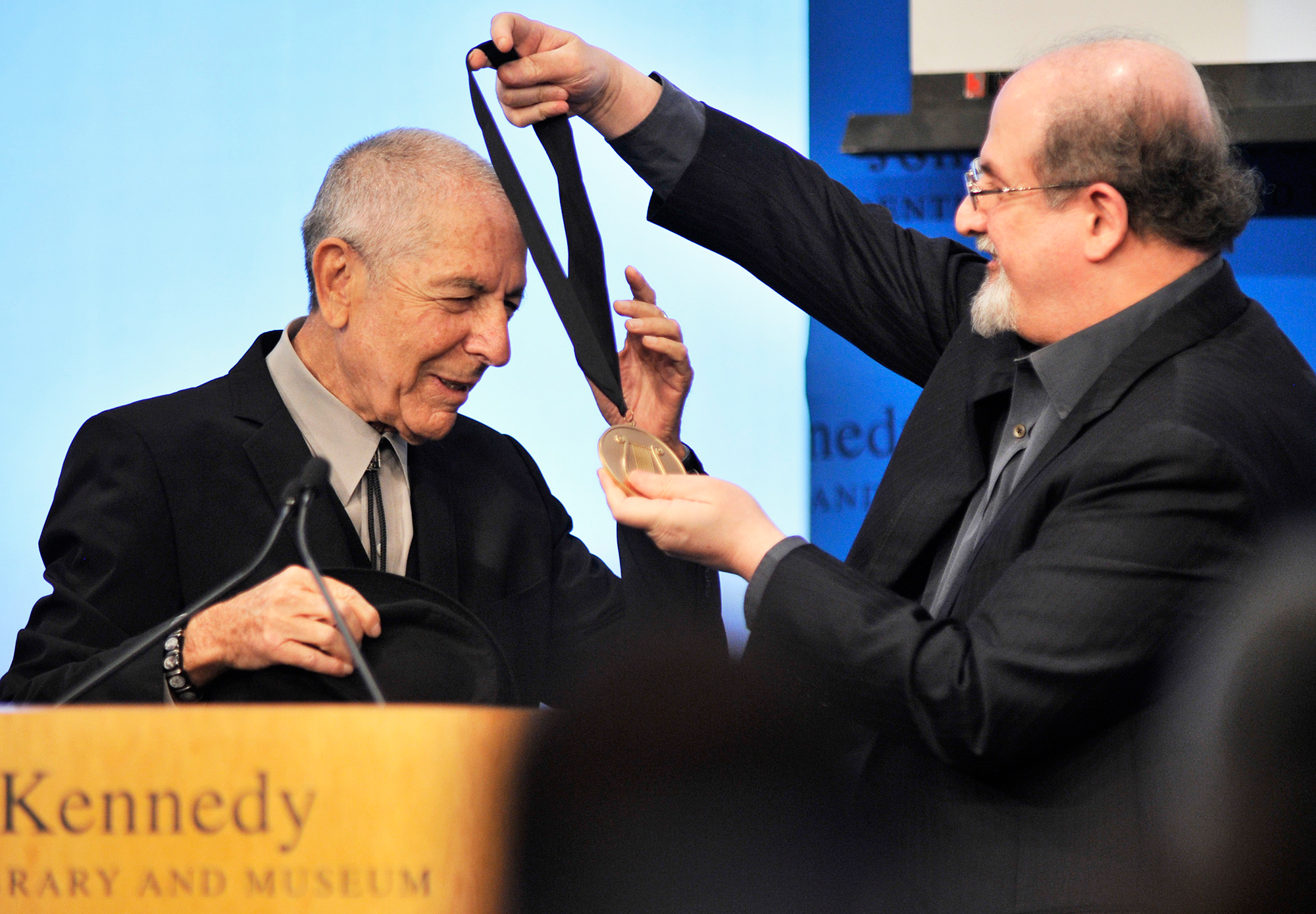 Leonard Cohen accepts an award presented by Salman Rushdie at the John F. Kennedy Presidential Library and Museum in Boston, on Feb. 26, 2012.