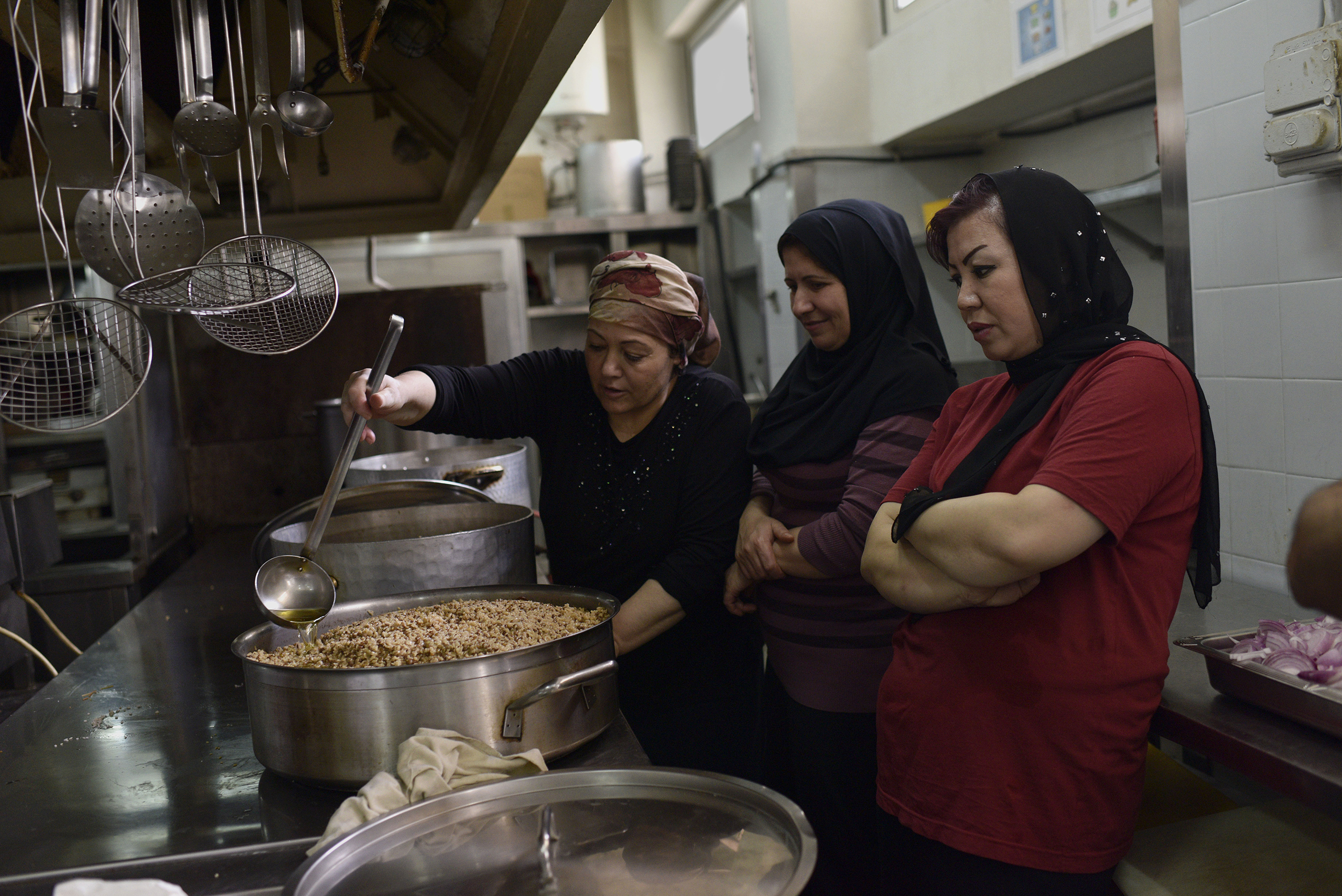 Women who made it out of some of the world's worst conflicts, like Syria and Afghanistan, cook alongside one another in the industrial kitchen of the City Plaza hotel.