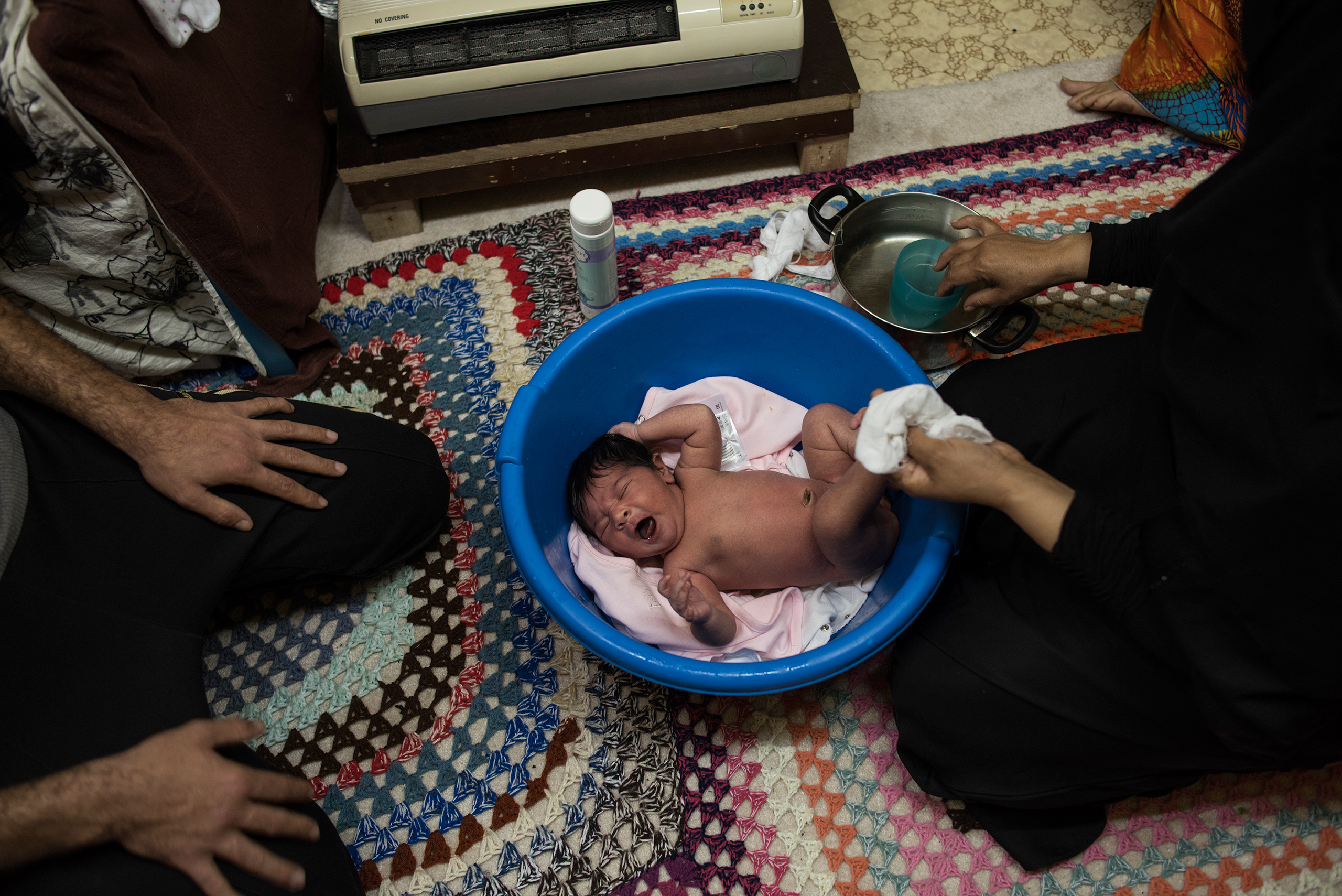 Syrian refugee Hayat bathes baby Rahaf, born one week earlier, next to a heater, at the Oreokastro camp in Thessaloniki, Greece, on Nov. 8, 2016. Rahaf was born to Noor Alhouda Talaa, 22, and Yusuf Arsan, 27.