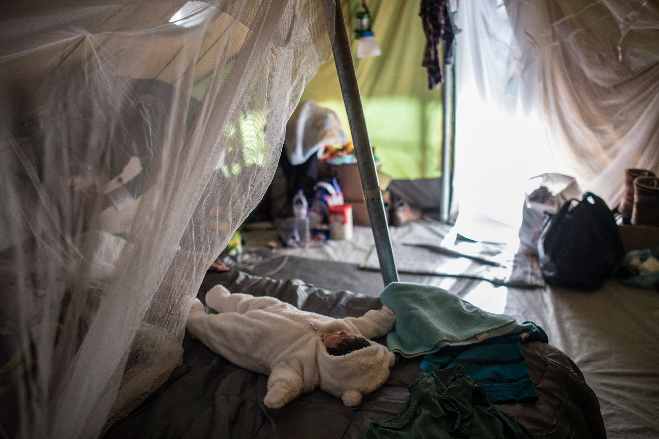 "Syrian refugee Tayma Abzali, 24, straightens up her tent as her baby, Helen, born on Sept. 13, sleeps in a warm onesie at a camp in Thessaloniki, Greece, on Nov. 10, 2016. Tayma, like other refugee mothers living in tents, is concerned about the onset of winter and cold temperatures in the tents—€""particularly those with new babies."
