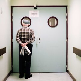 A resident stands in front of the ward's locked exit door. Passages are blocked and doors are locked to prevent residents from wandering off.