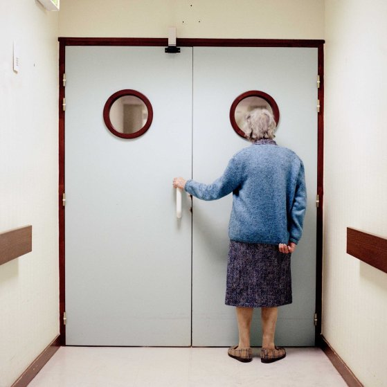 A resident stands in front of the ward's locked exit door
