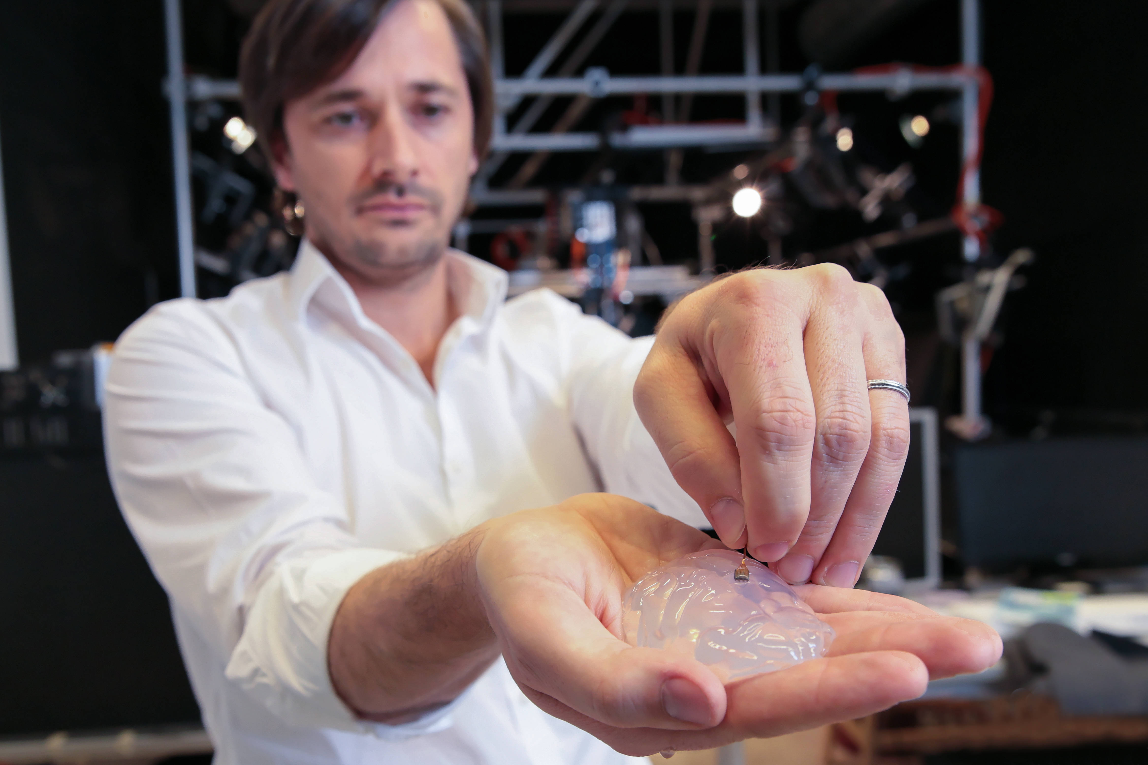 Grégoire Courtine holds a silicon model of a primate's brain and a brain implant. The brain-spine interface uses a microelectrode array like this one to detect spiking activity of the brain's motor cortex