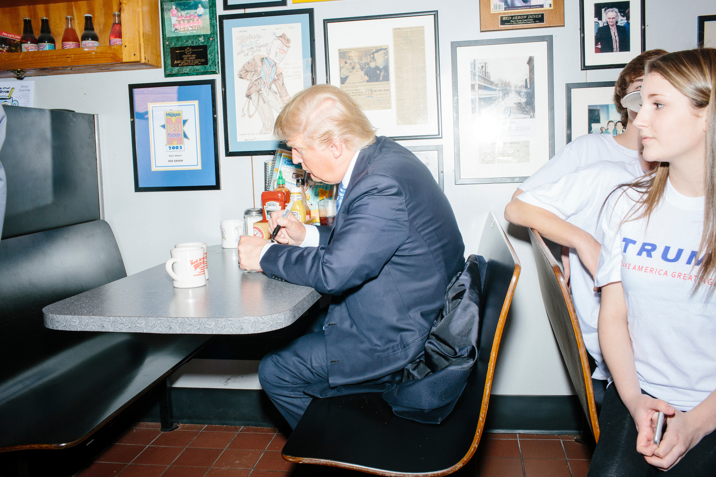 Republican presidential candidate Donald Trump autographs diner mugs after speaking to reporters at the Red Arrow Diner in Manchester, New Hampshire.
