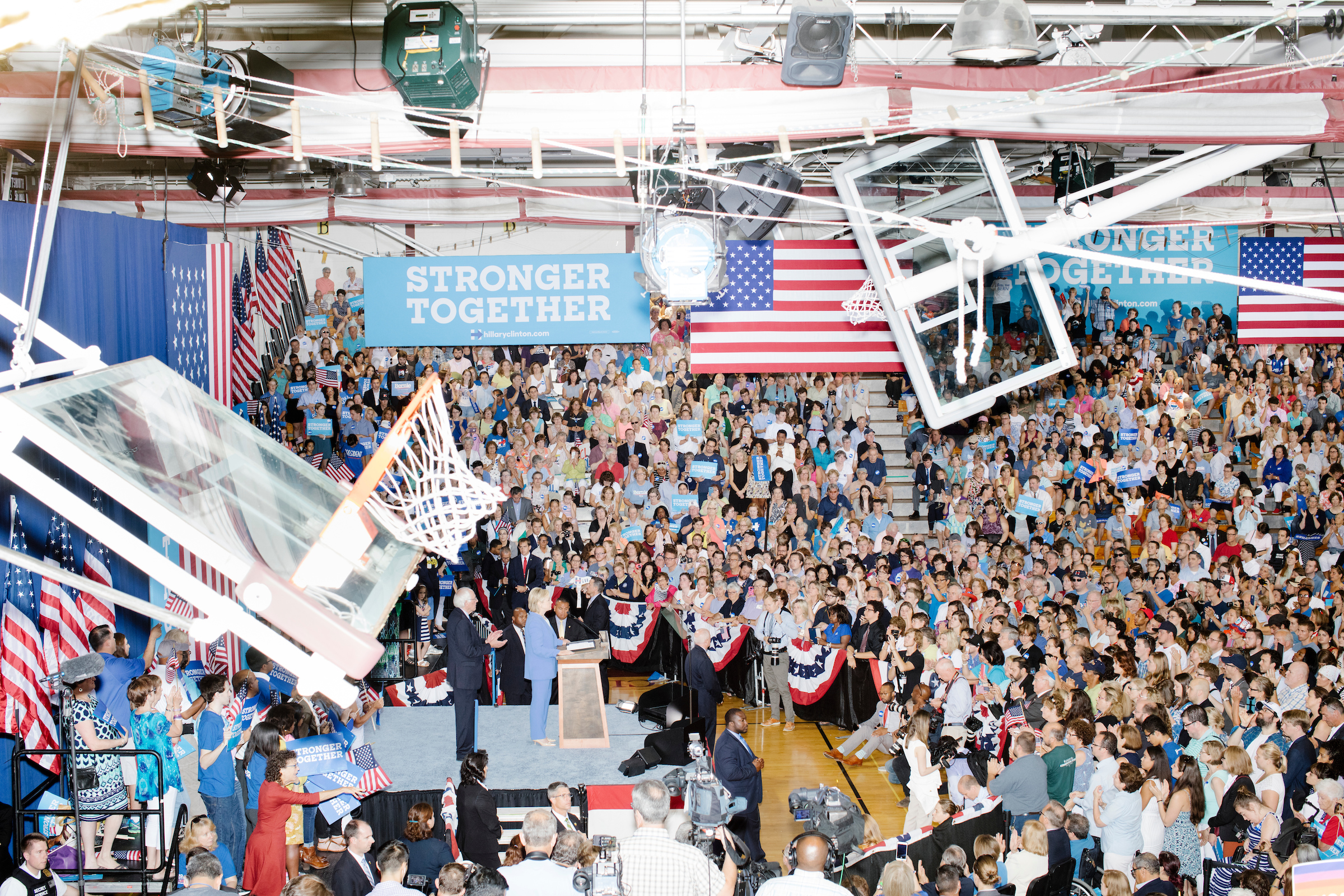 Hillary Clinton speaks during a rally while former rival Bernie Sanders stands on stage at Portsmouth High School in Portsmouth, New Hampshire, on July 12, 2016. At the rally, Sanders officially endorsed Clinton as the Democratic nominee for president.