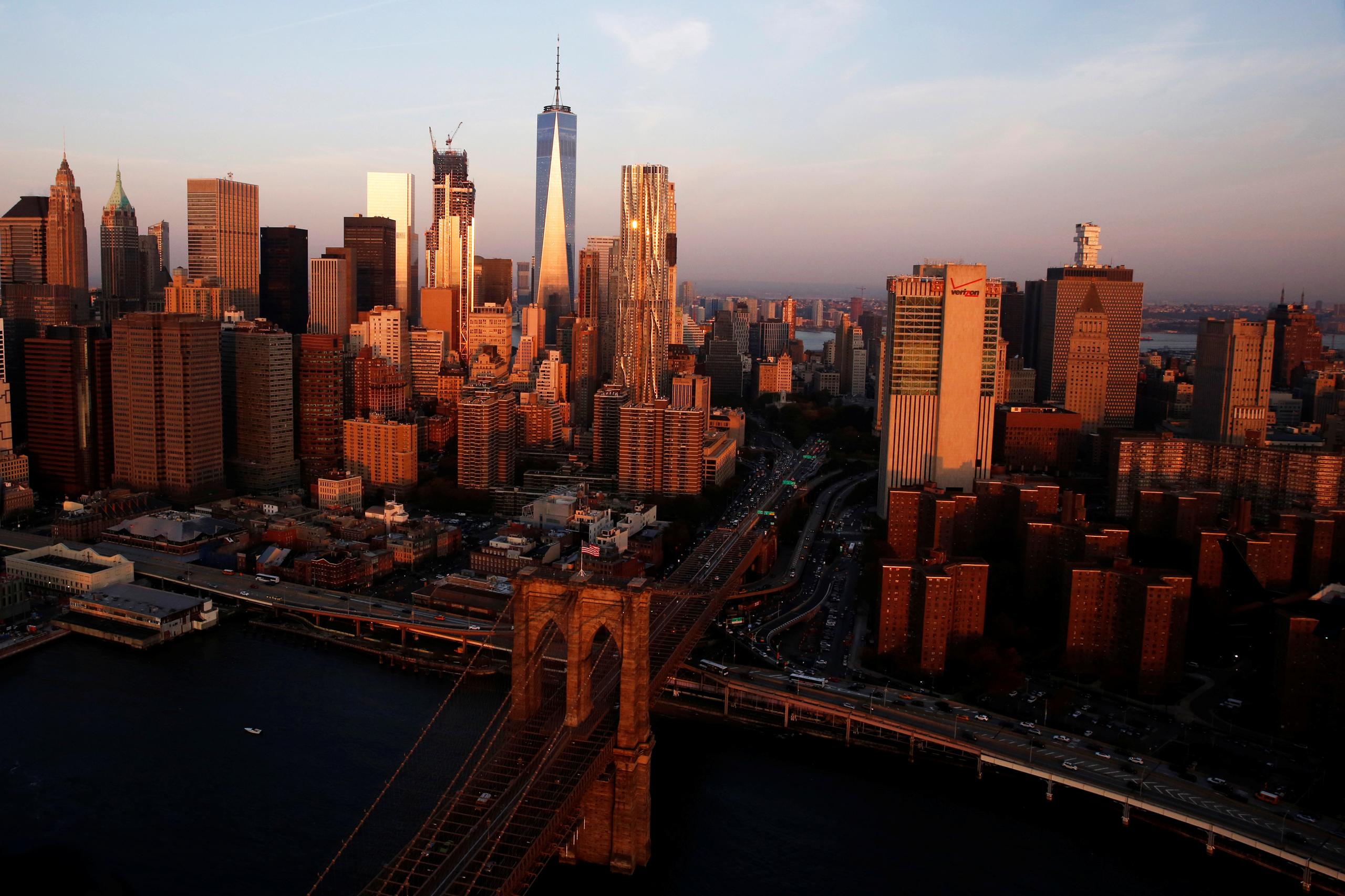 The rising sun lights the Brooklyn Bridge and One World Trade in the Manhattan borough of New York City on Nov. 2, 2016.