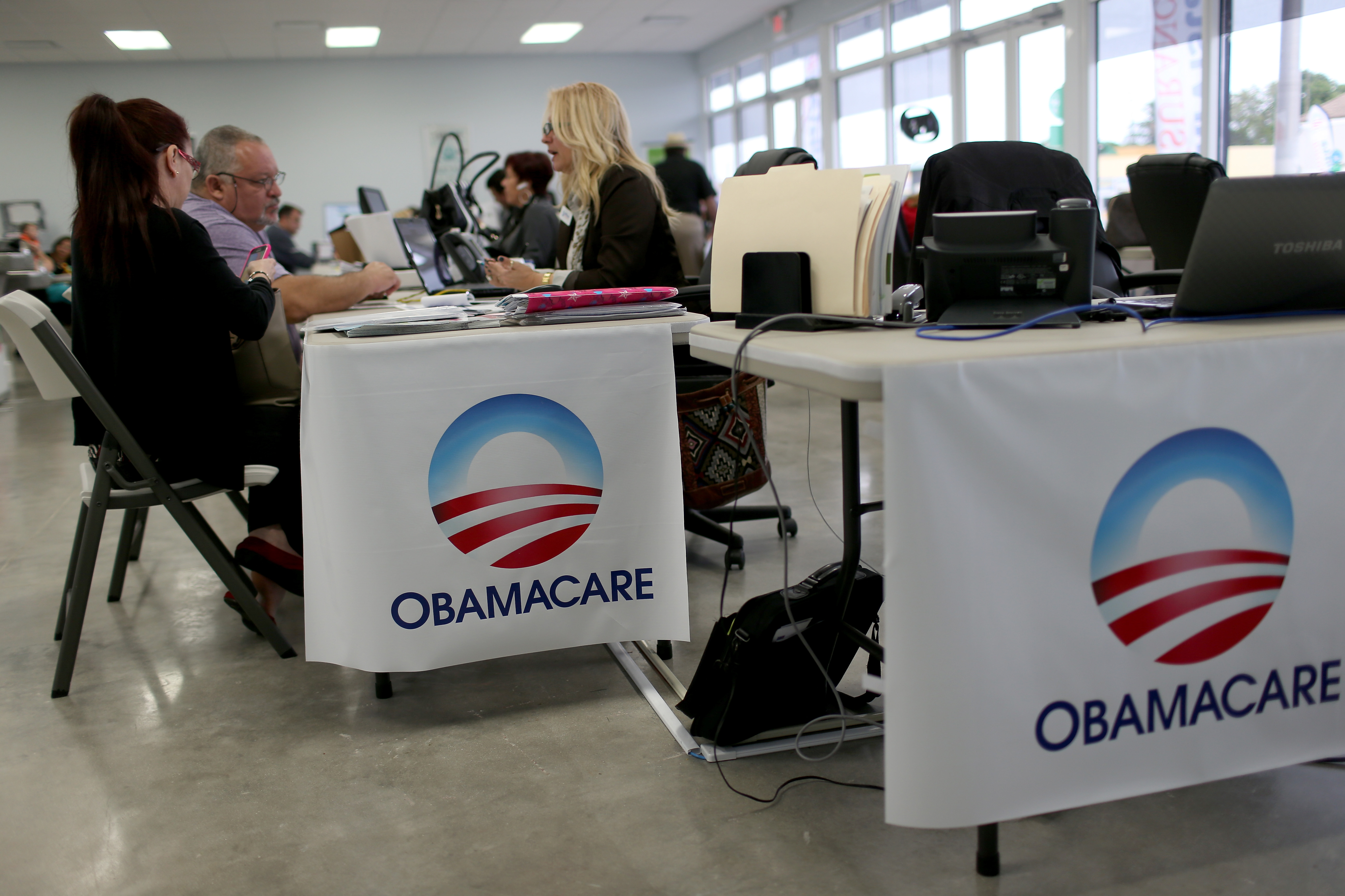 Aymara Marchante (L) and Wiktor Garcia sit with Maria Elena Santa Coloma, an insurance advisor with UniVista Insurance company, as they sign up for the Affordable Care Act, also known as Obamacare, before the February 15th deadline on February 5, 2015 in Miami, Florida.