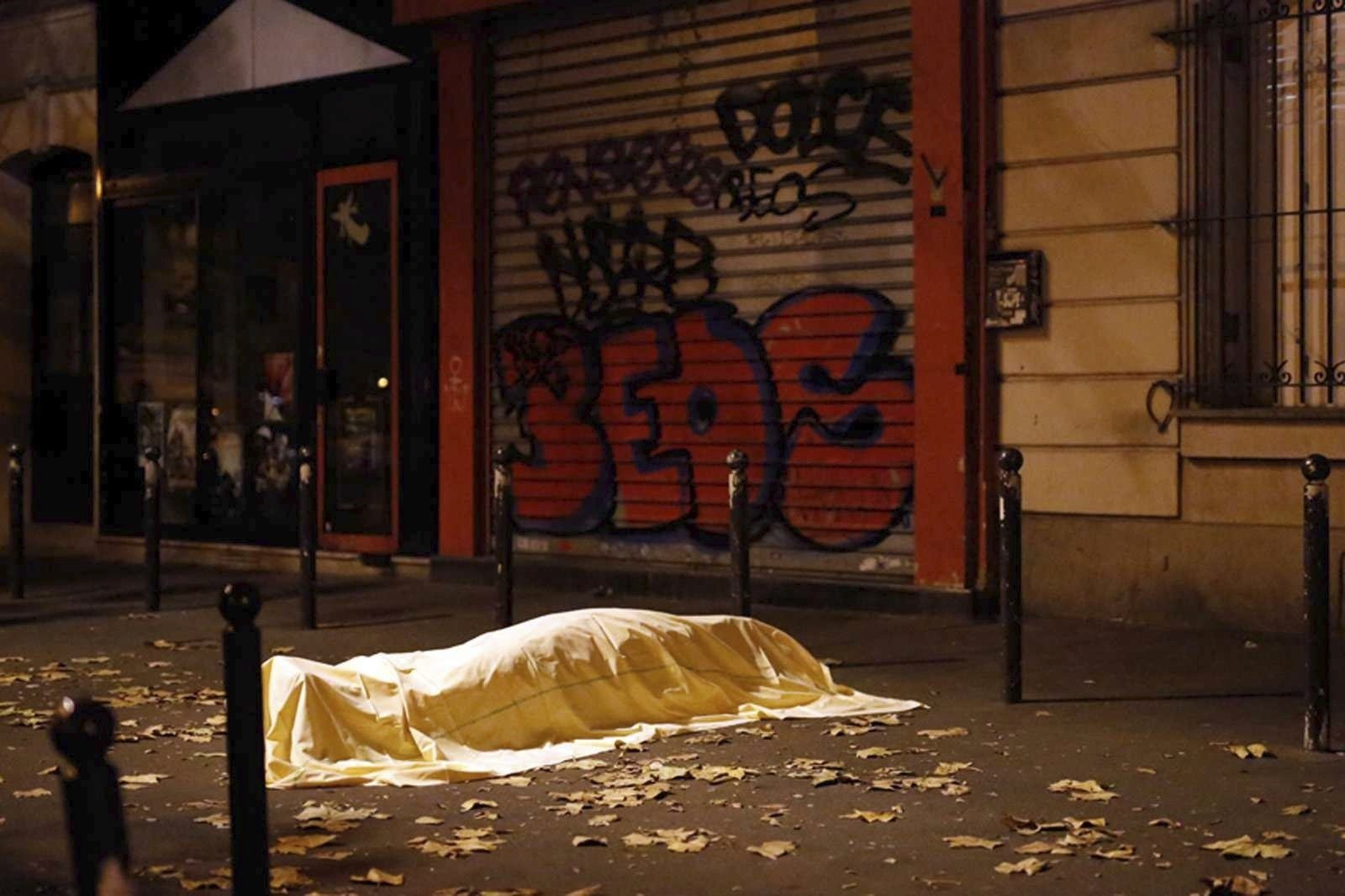 A victim under a blanket lays dead outside the Bataclan theater in Paris. Nov. 13, 2015.