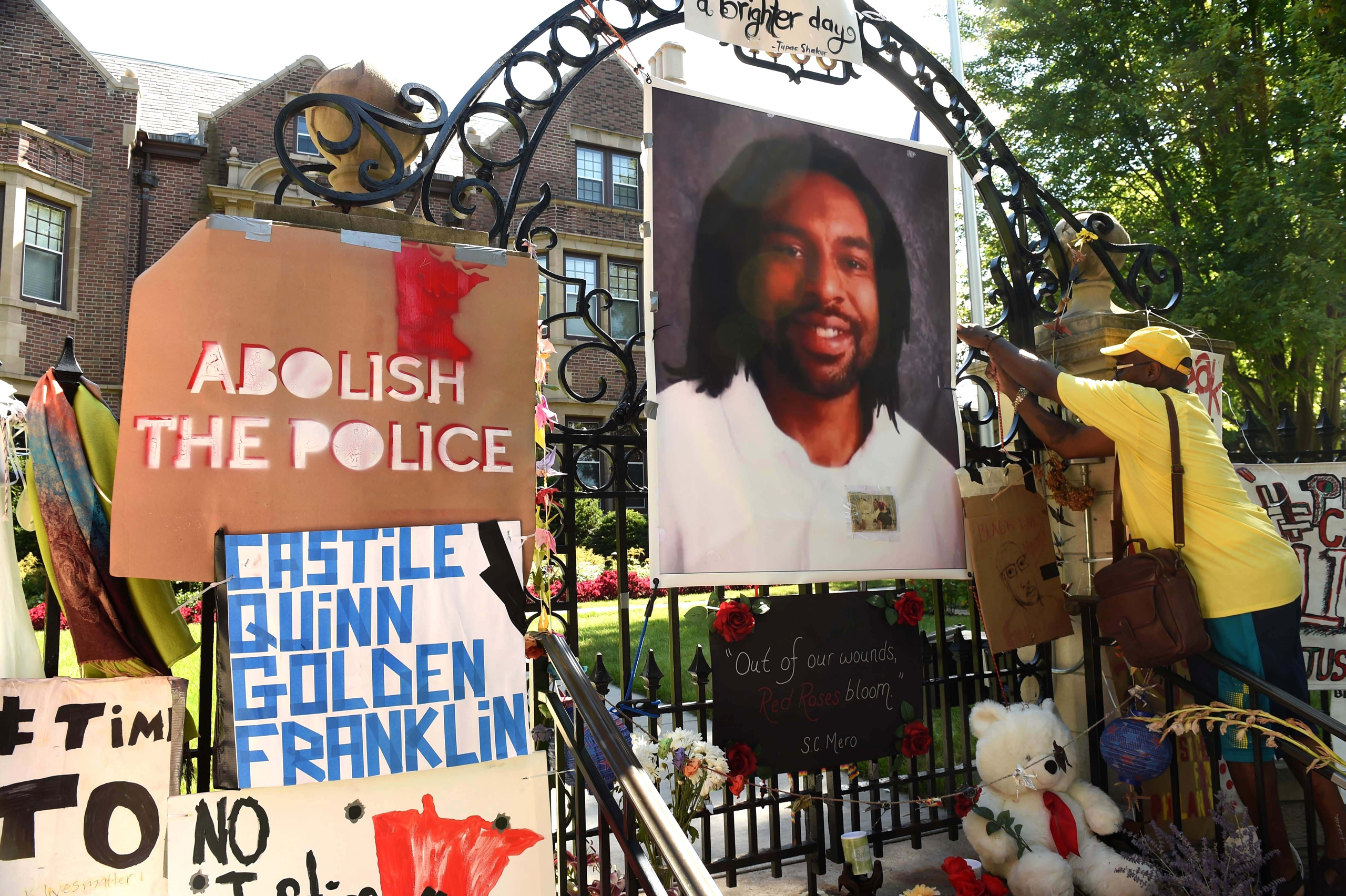 King Demetrius Pendleton hangs a sign on the gate of the Governor's Residence as protesters demonstrate against the shooting death of Philando Castile by a St. Anthony police officer, in St. Paul, Minn., on July 24, 2016.