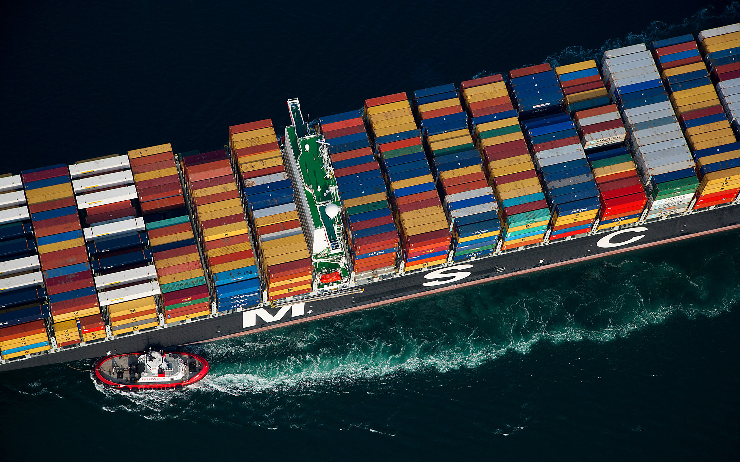 A tugboat guides a ship loaded with freight containers near the Port of Long Beach, Calif.