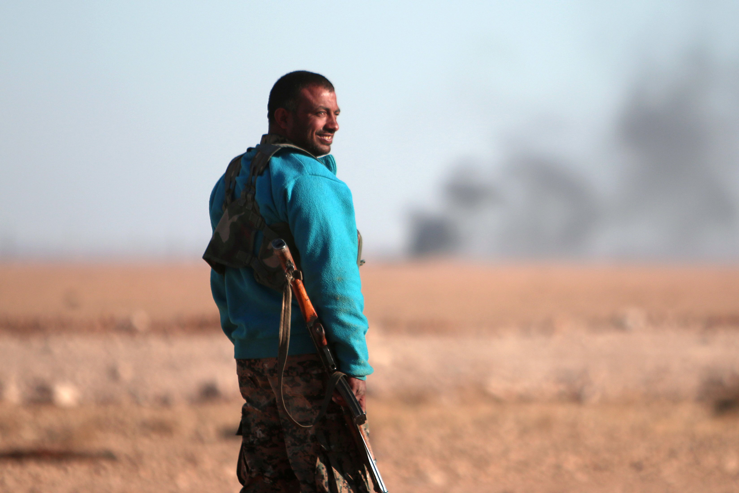A Syrian Democratic Forces (SDF) fighter stands near rising smoke, north of Raqqa city, Syria, on Nov. 6, 2016.
