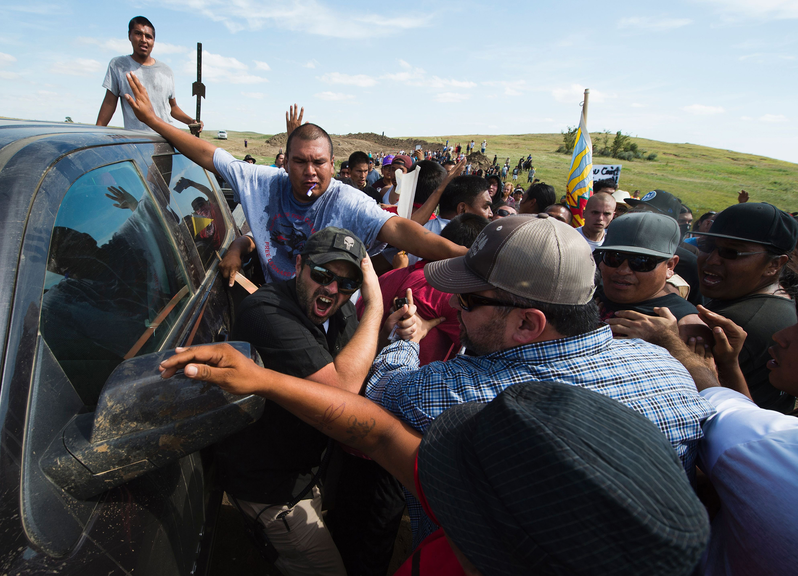 Protesters protect a security contractor from other protesters                      on Sept. 3