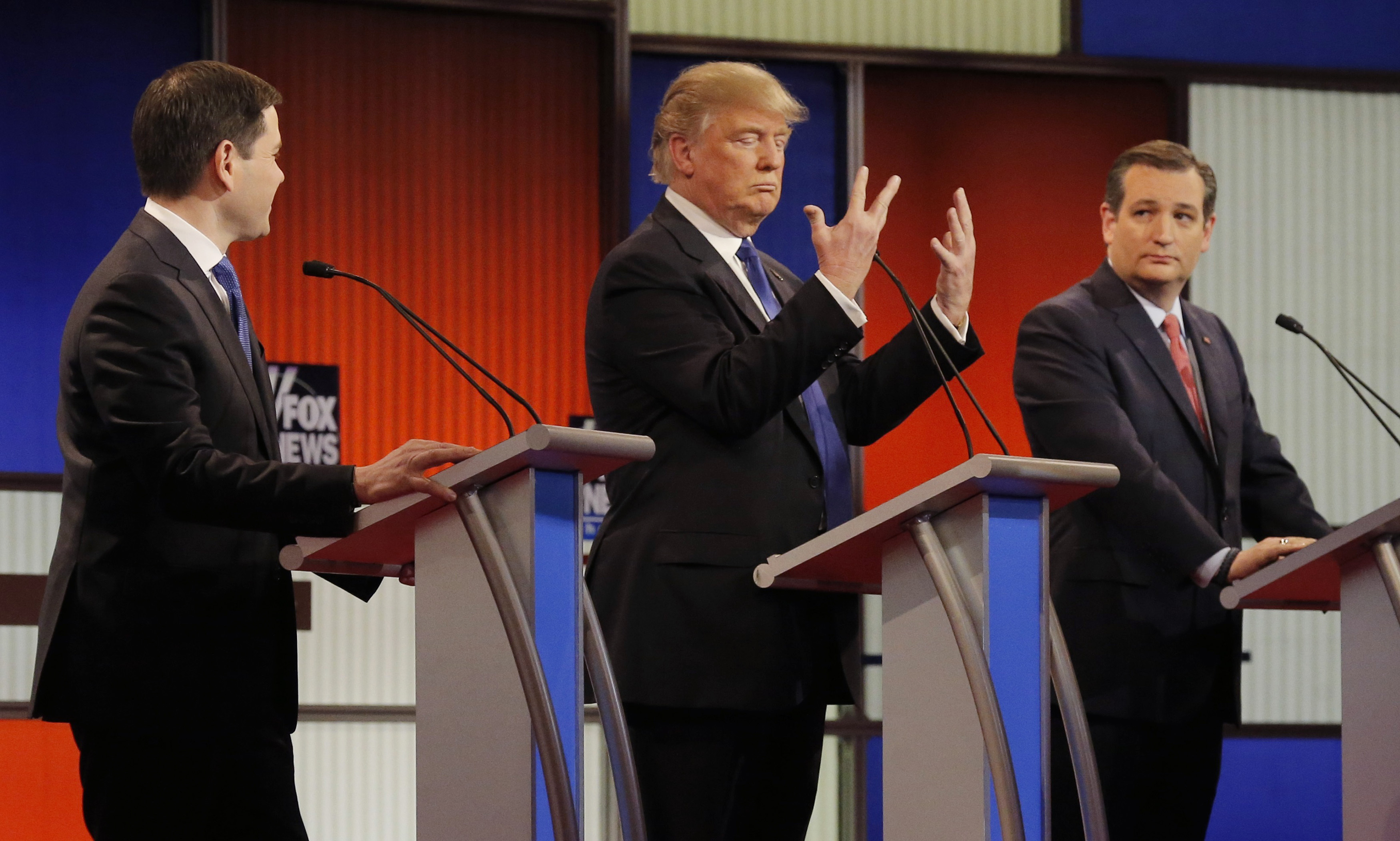 Republican U.S. presidential candidate Donald Trump shows off the size of his hands as rivals Marco Rubio (L) and Ted Cruz (R) look on at the start of the U.S. Republican presidential candidates debate in Detroit, Michigan, on March 3, 2016.