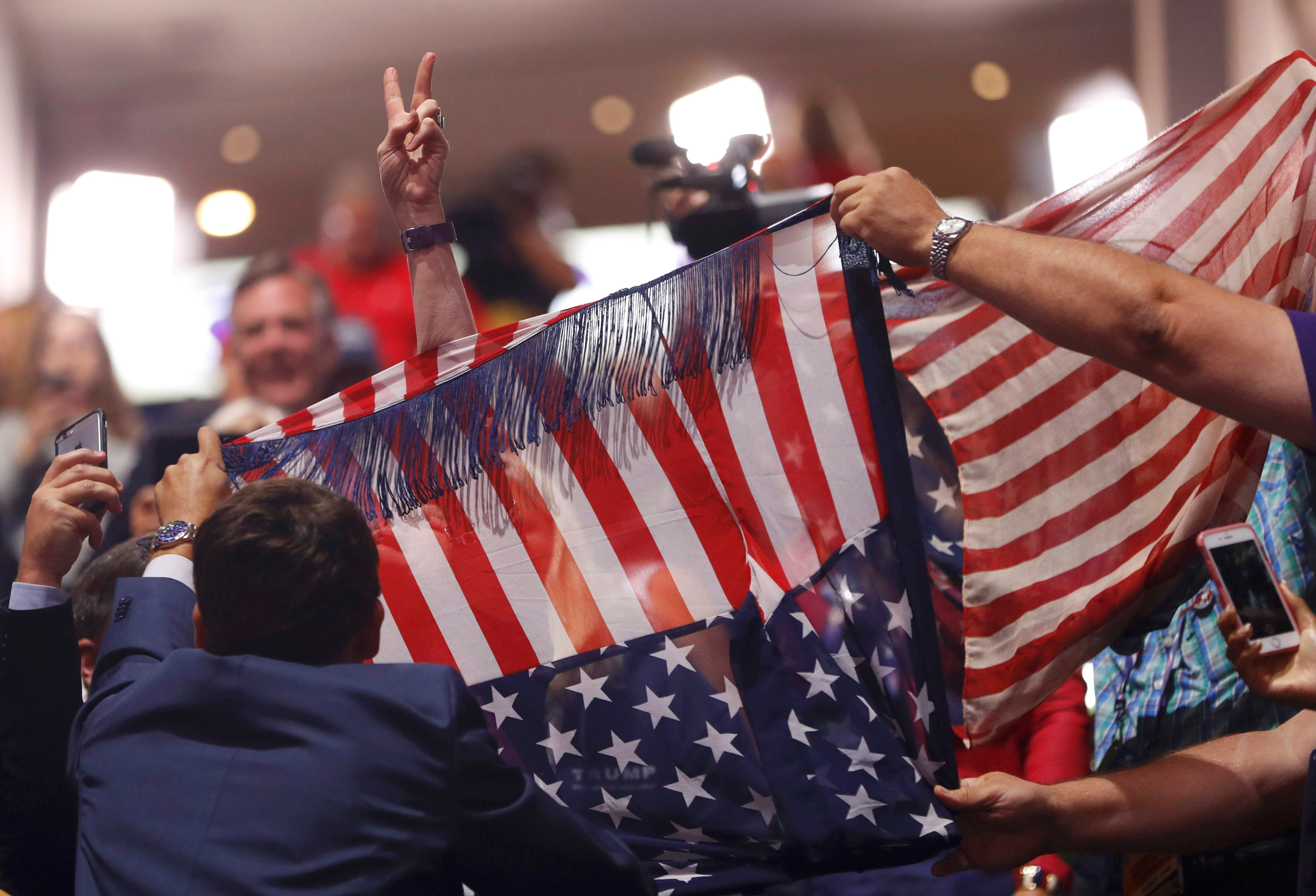 Supporters of Donald Trump attempt to obscure a protestor from the activist group Code Pink, who is holding an anti-racism and anti-hate banner, as she interrupts the proceedings during the second day of the Republican National Convention in Cleveland, Ohio, on July 19, 2016.