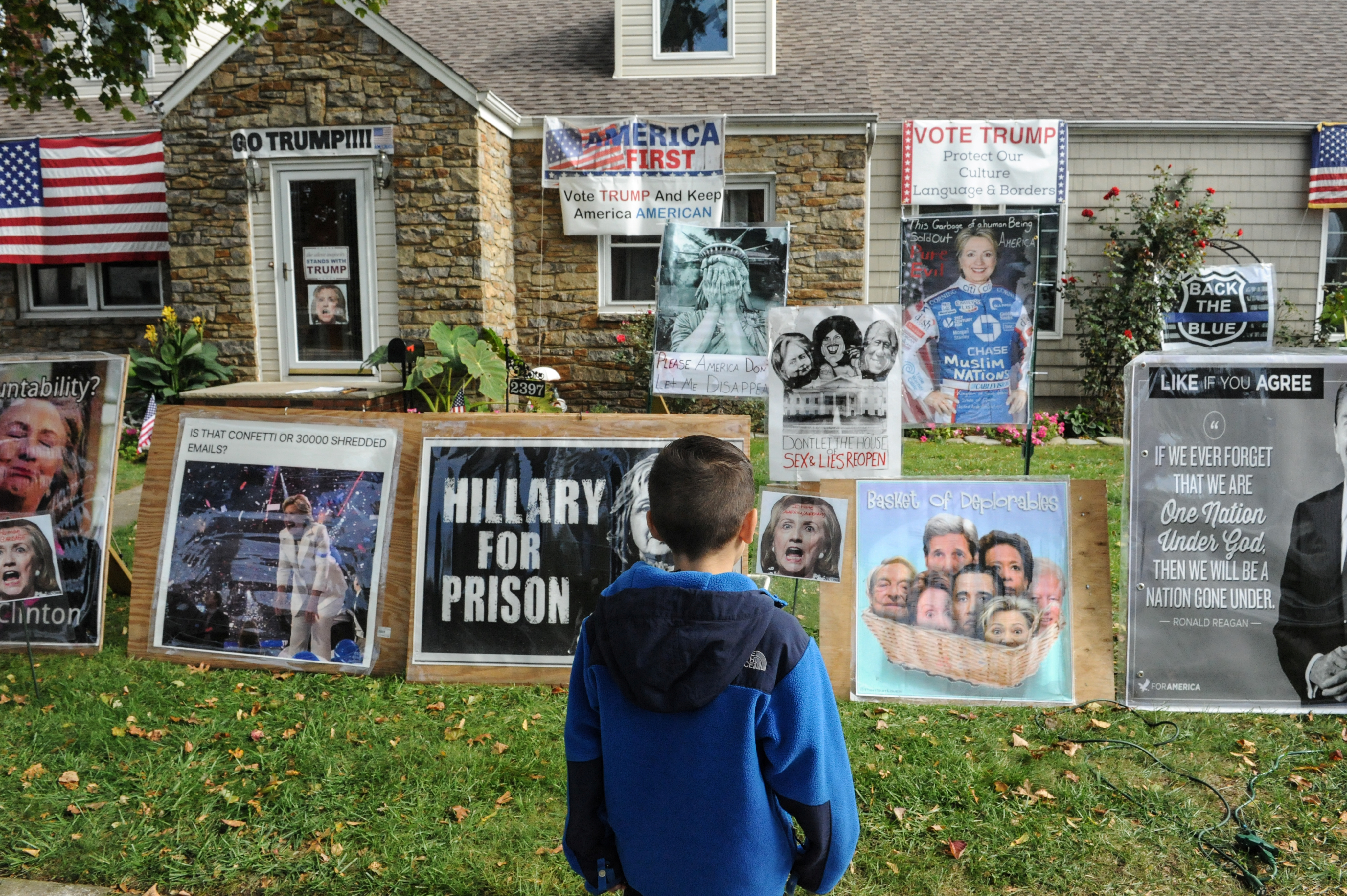 Dominick Vaglica, 7, looks at a home displaying signs supporting Donald Trump and criticizing Hillary Clinton in Bellmore, NY, on Oct. 29, 2016.