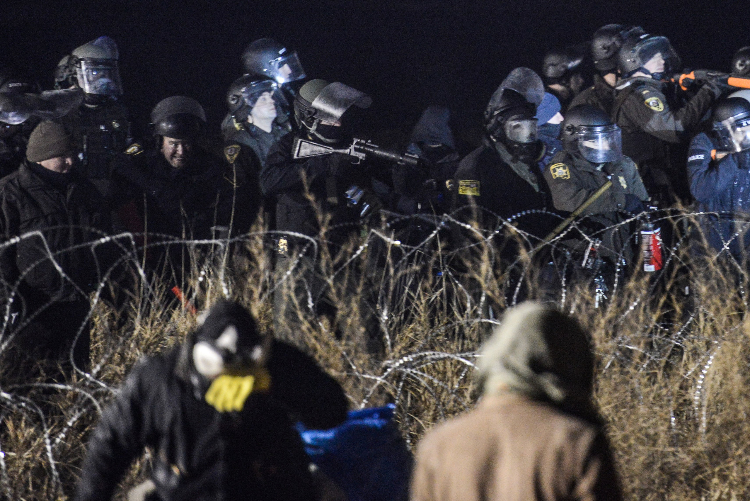 Police confront protesters with a rubber bullet gun during a protest against plans to pass the Dakota Access pipeline near the Standing Rock Indian Reservation, near Cannon Ball, N.D., on Nov. 20, 2016.