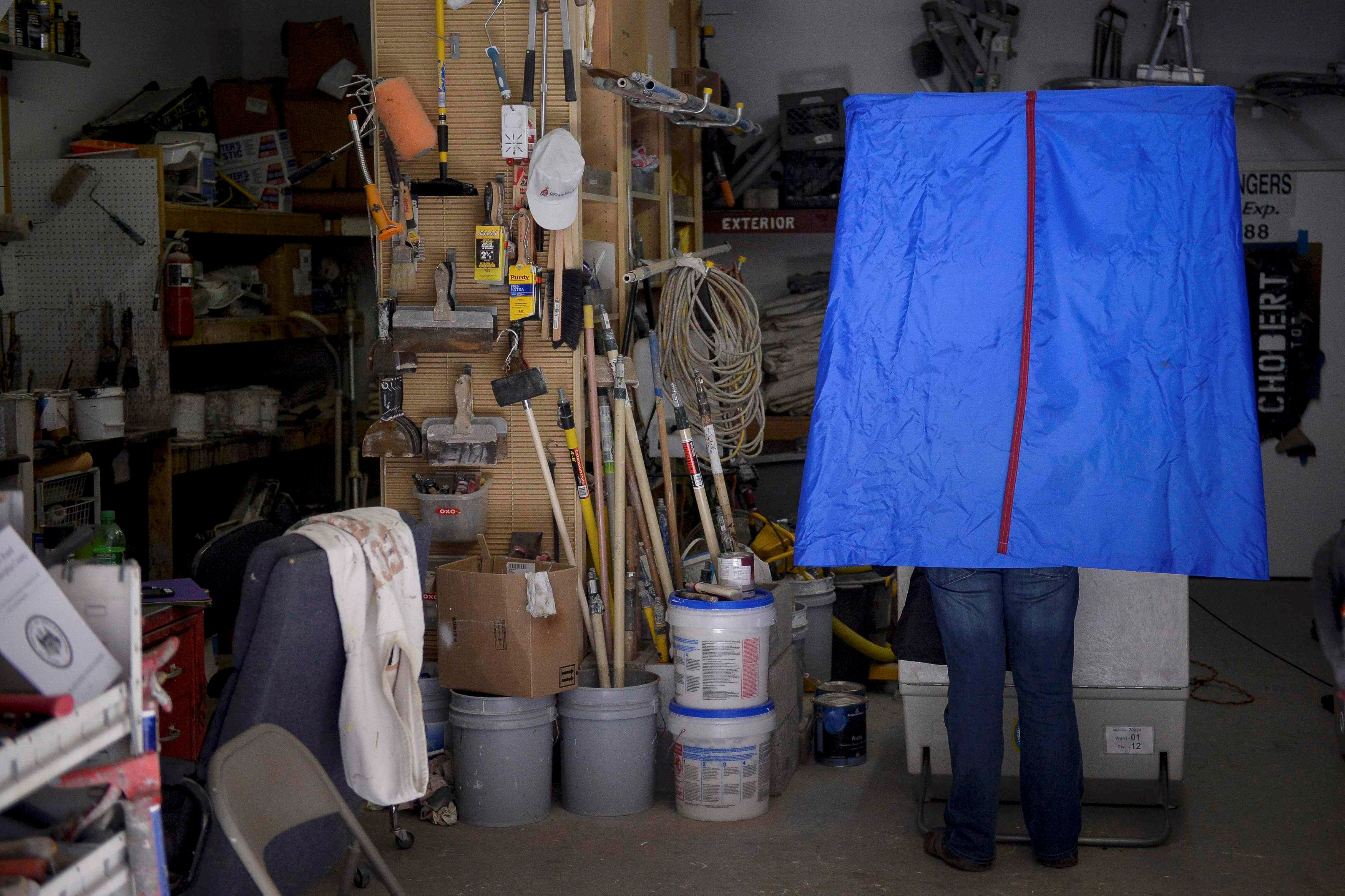 A voter casts his ballot inside the garage of Chobert Decorators in Philadelphia.