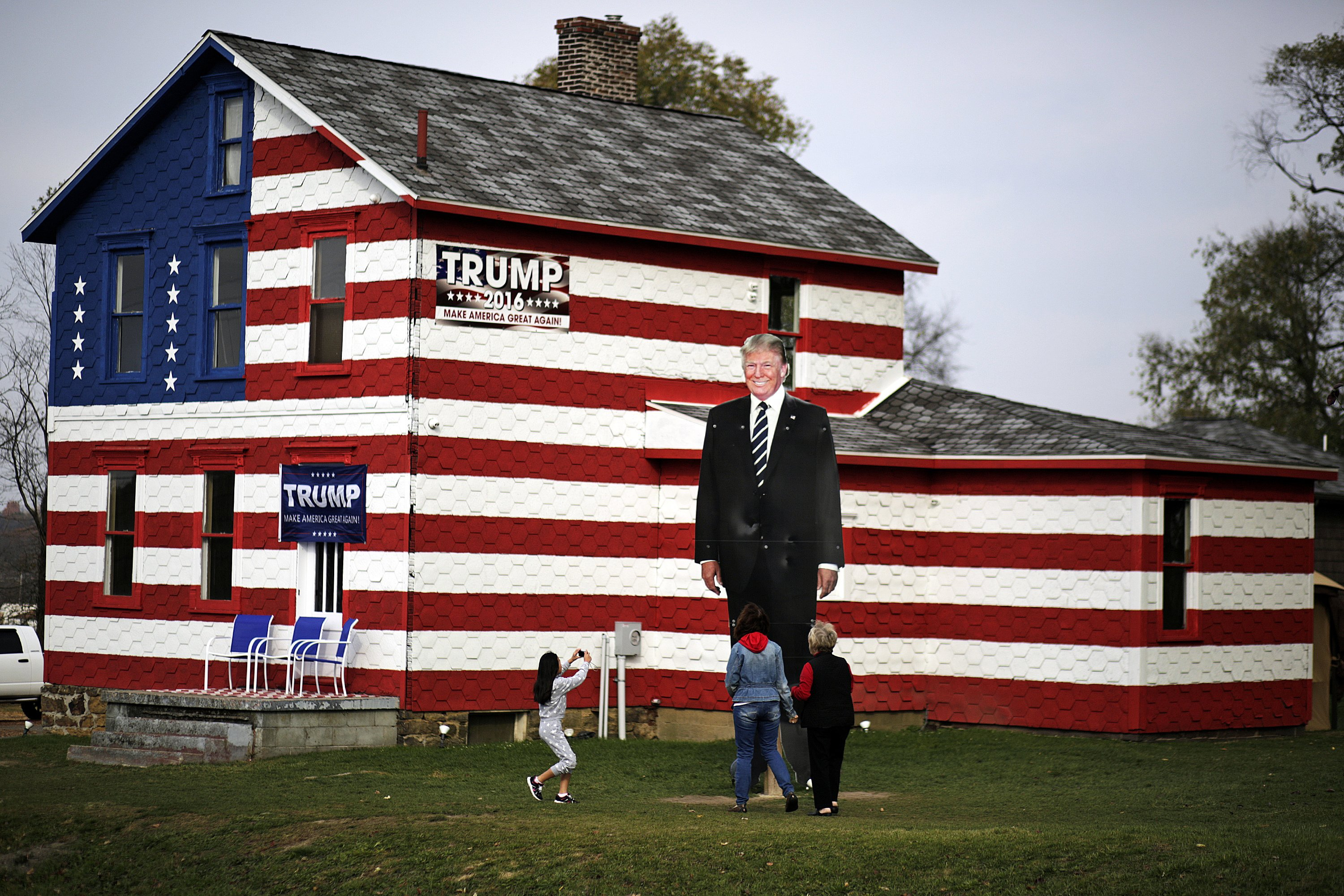 Visitors take photos of a giant cutout of Donald Trump in front of the Trump House owned by Lisa Rossi in Youngstown, Pa. on Nov. 8, 2016.