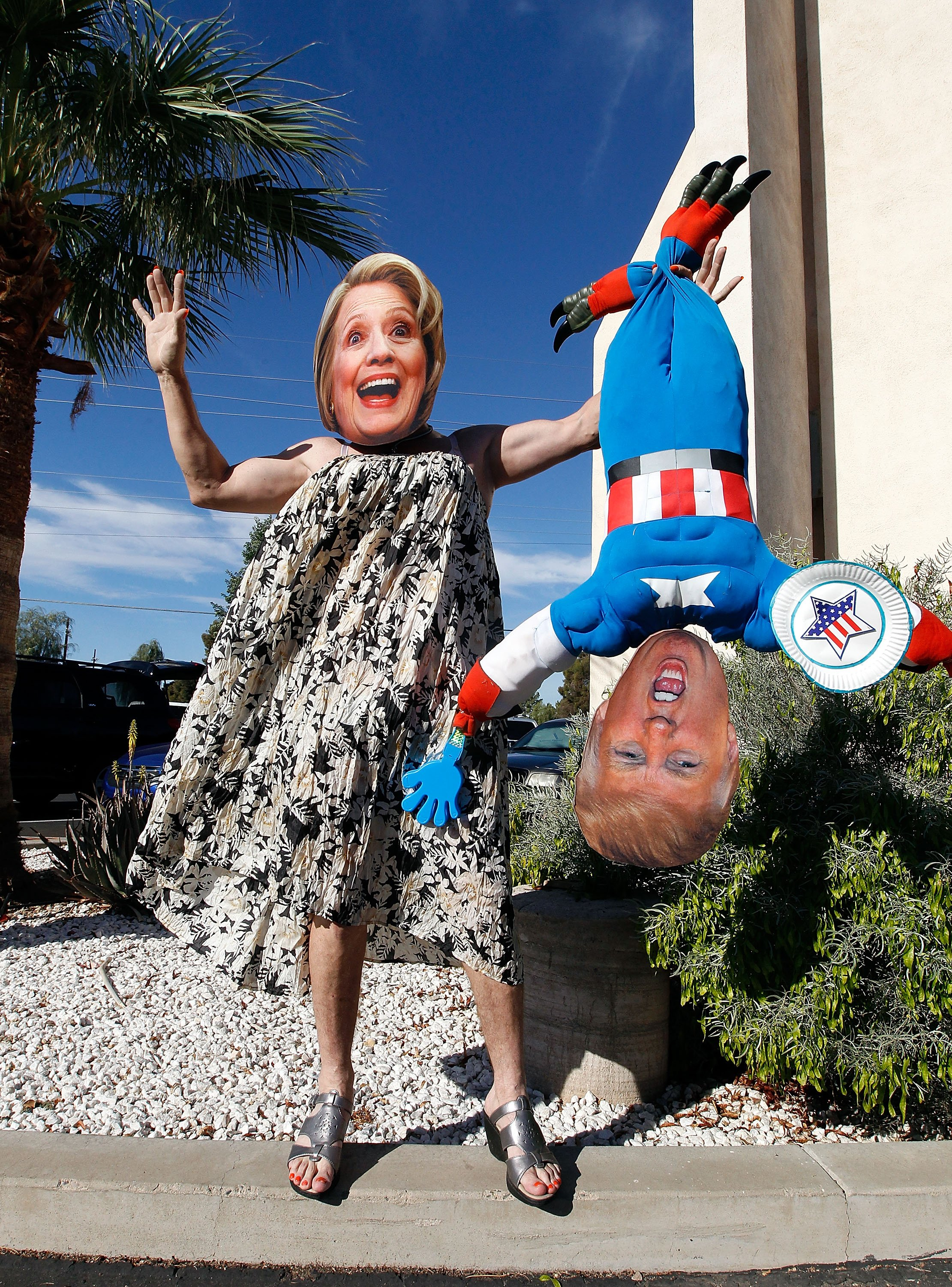 Hillary Clinton supporter Jorge Mendez of Glendale, Arizona wears a dress and Hillary Clinton mask while holding a makeshift doll of Donald Trump after voting in Phoenix.