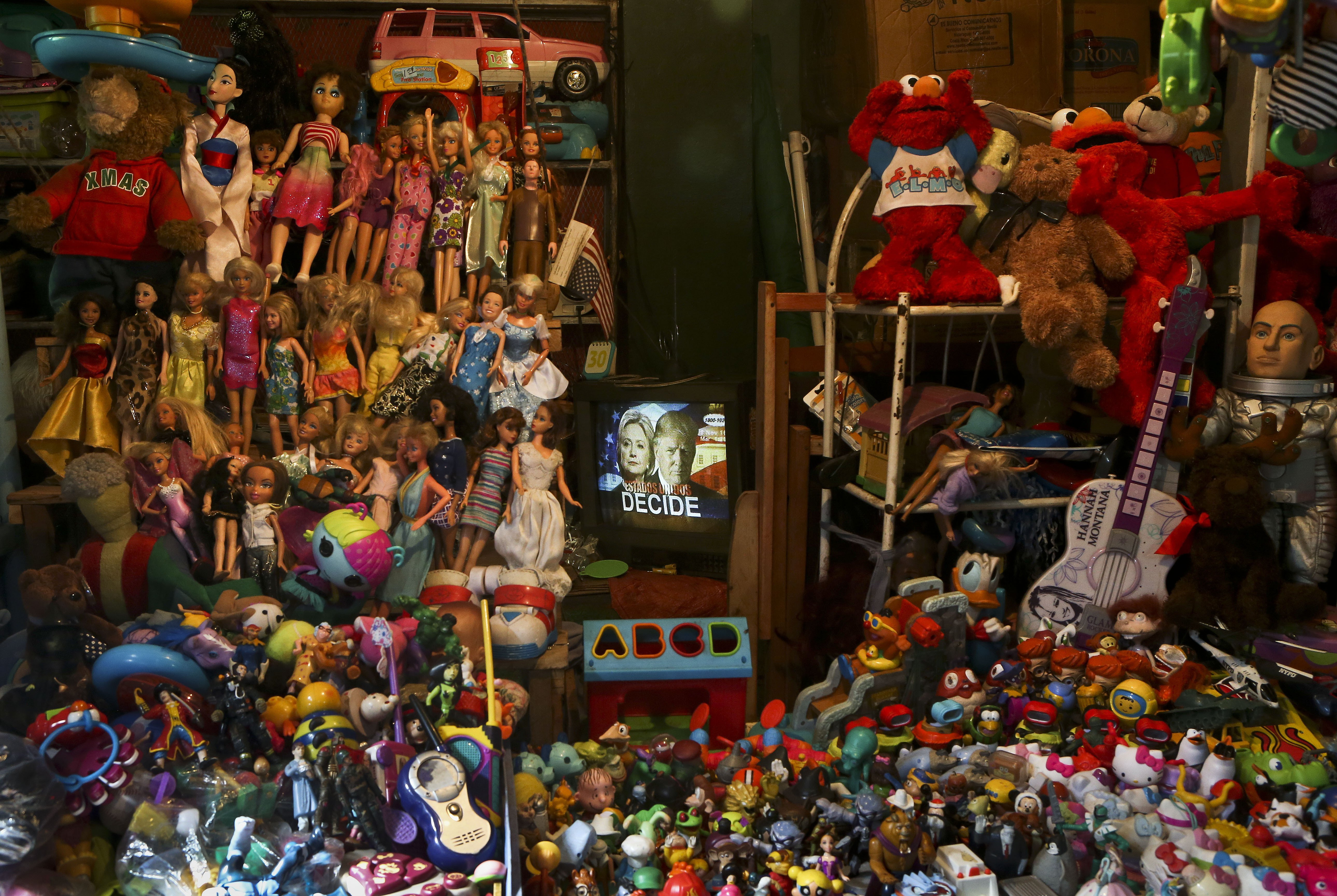 Presidential candidates on a TV screen during a Nicaraguan newscast surrounded by toys and puppets at a market in Managua, Nicaragua,