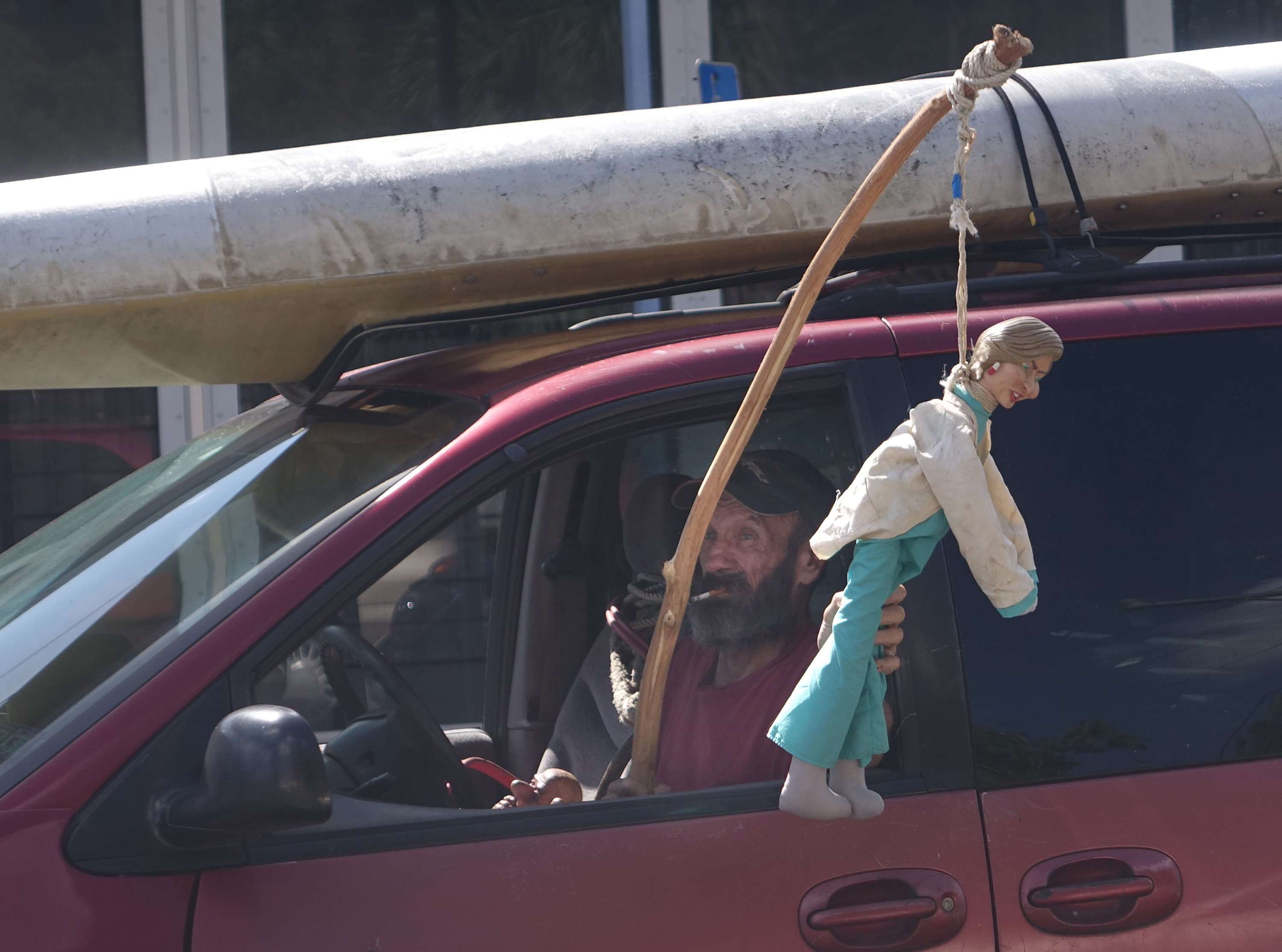 An anti-Clinton supporter holds a Clinton doll hanged on a noose out of his car as he drives by the Emma Loum Olson Civic Center in Pompano Beach, Fla.