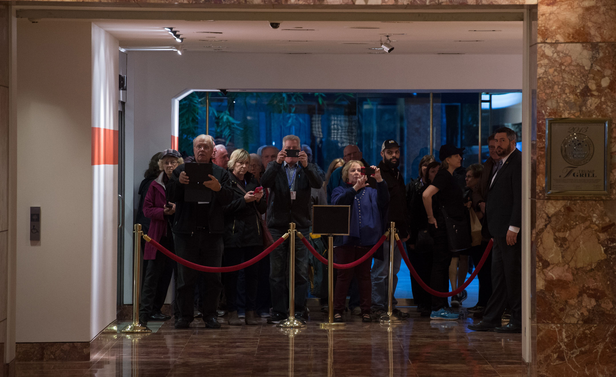 Visitors take photos from behind velvet ropes of the lobby in Trump Tower, on Nov. 13, 2016.