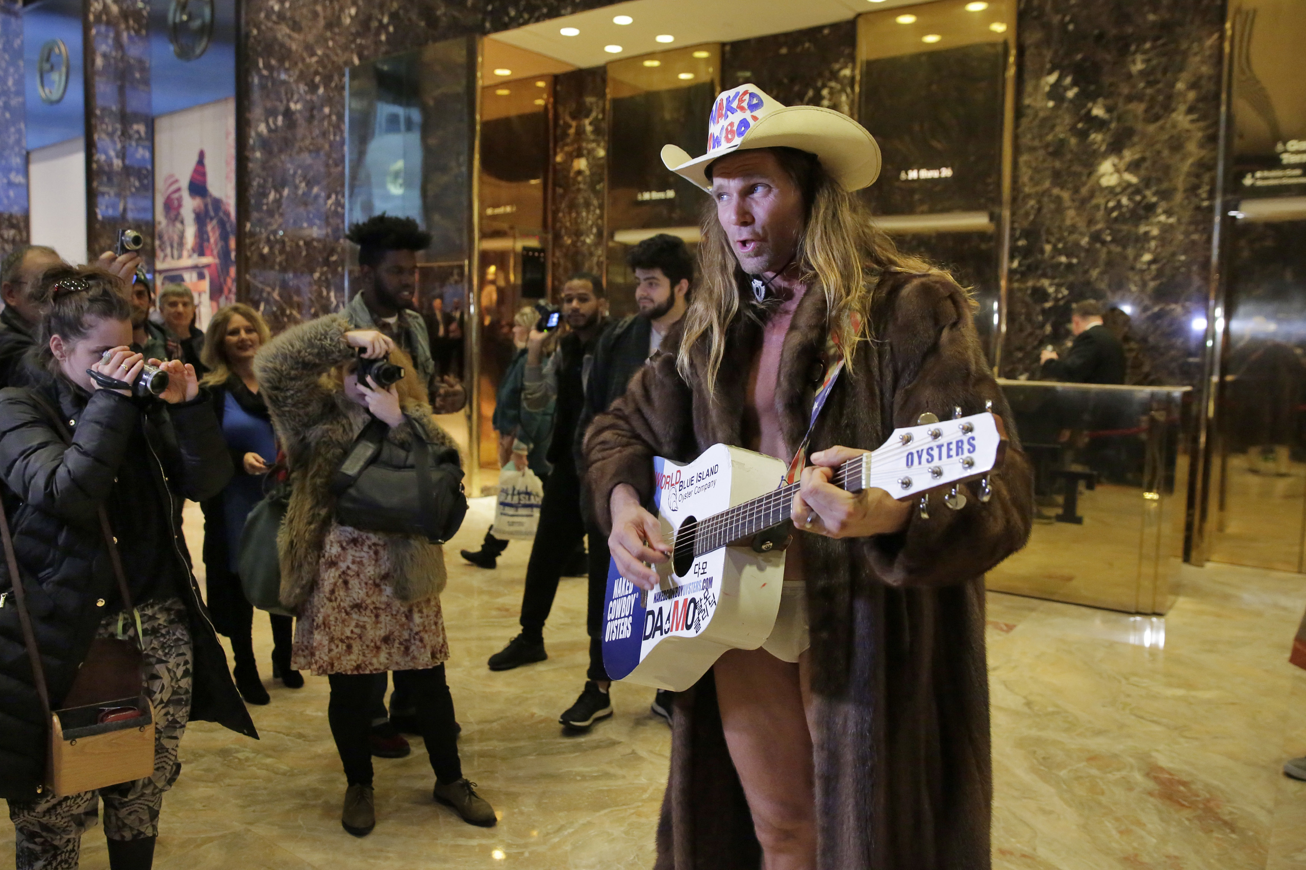 Robert Burck, who portrays the Naked Cowboy, performs a Trump-themed song in the lobby of Trump Tower in New York, on Nov. 18, 2016.