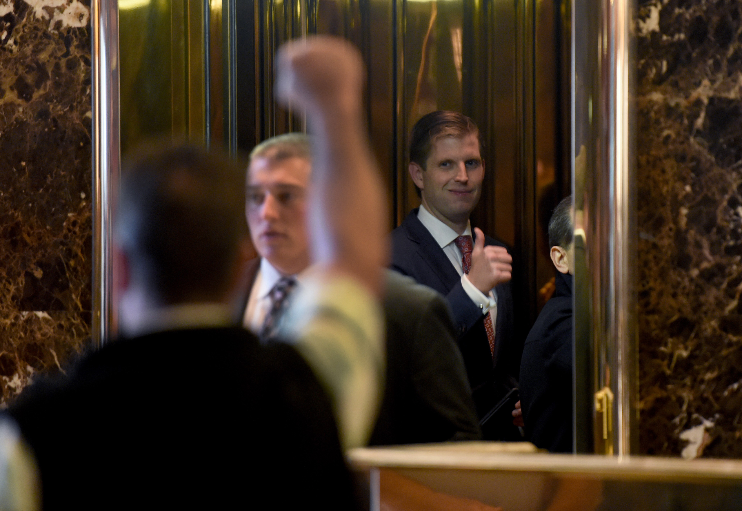 Eric Trump, son of US President-elect Donald Trump gives the thumbs-up to a supporter as he gets on the elevator at Trump Tower on  Nov. 11, 2016.