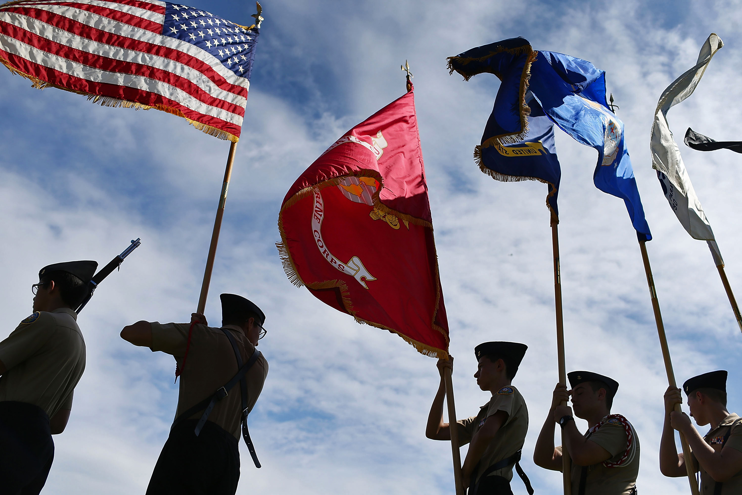 Members of the G. Holmes Braddock Senior High School NJROTC color guard carry their flags during a Veterans day ceremony in Miami Beach, Florida, on Nov. 11, 2015.