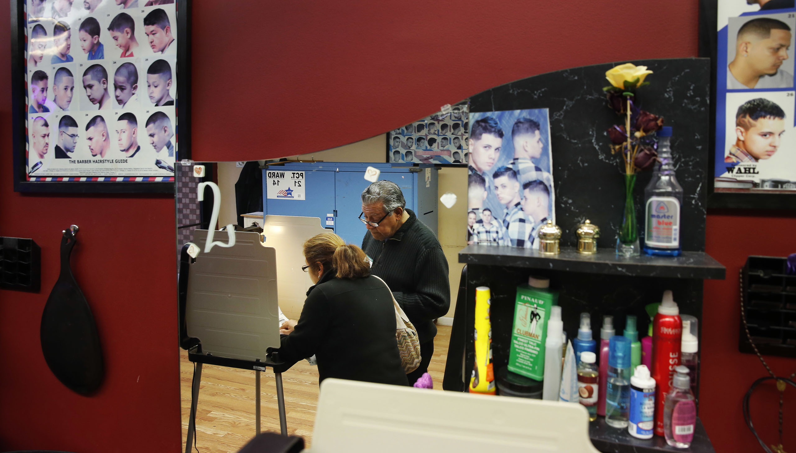 Democratic polling judge John Ramirez, right, is reflected in a mirror as he assists a voter as she fills out her ballot at Delia's Beauty Salon on Nov. 8, 2016, in Chicago.